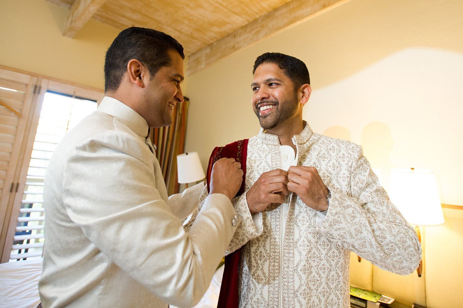 Groom getting help into his Sherwani before his Hindu wedding ceremony