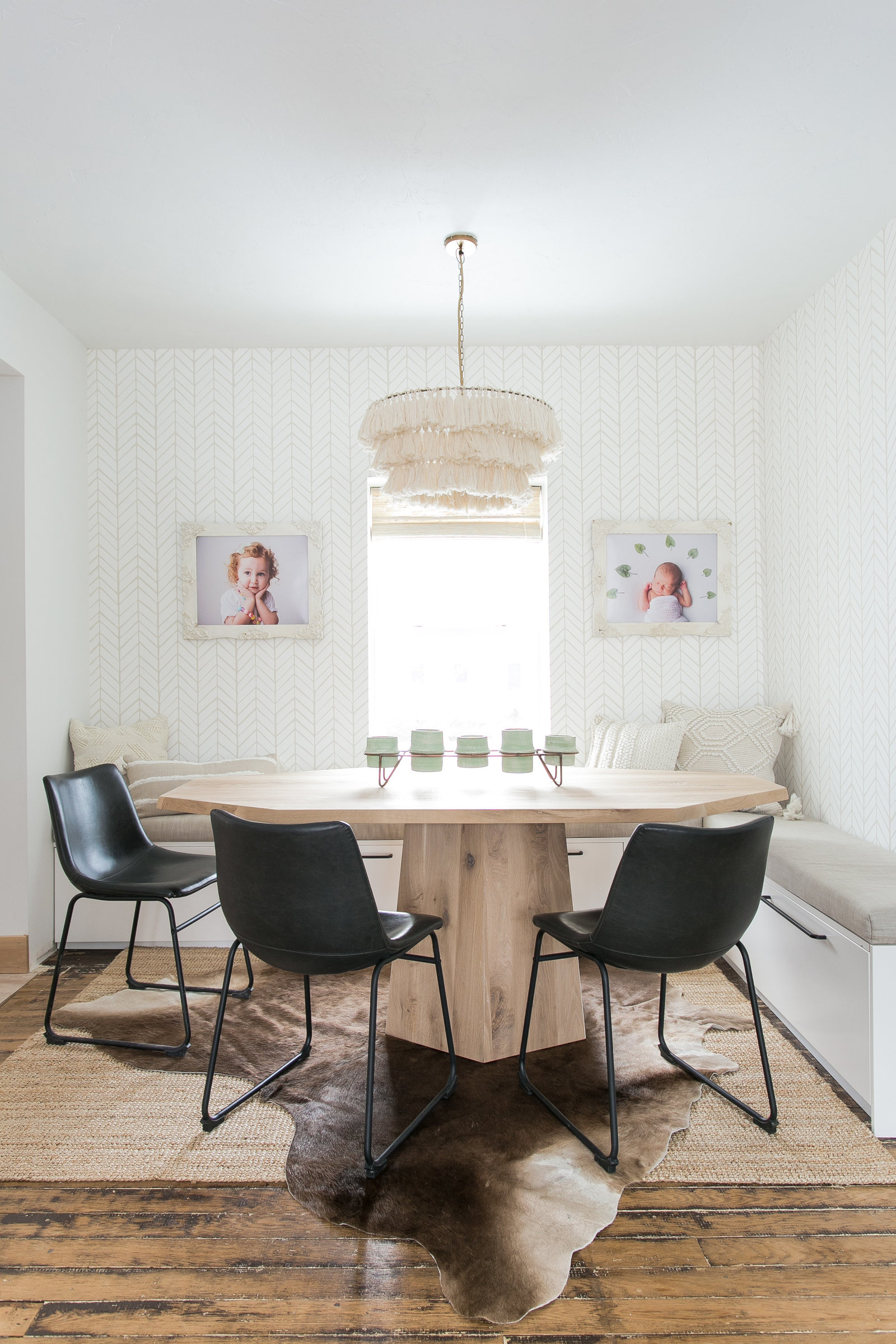 Modern dining room design with built in seating and storage.  Cream and white wallpaper design with tassel chandelier, cowhide rug and custom hexagon table.
