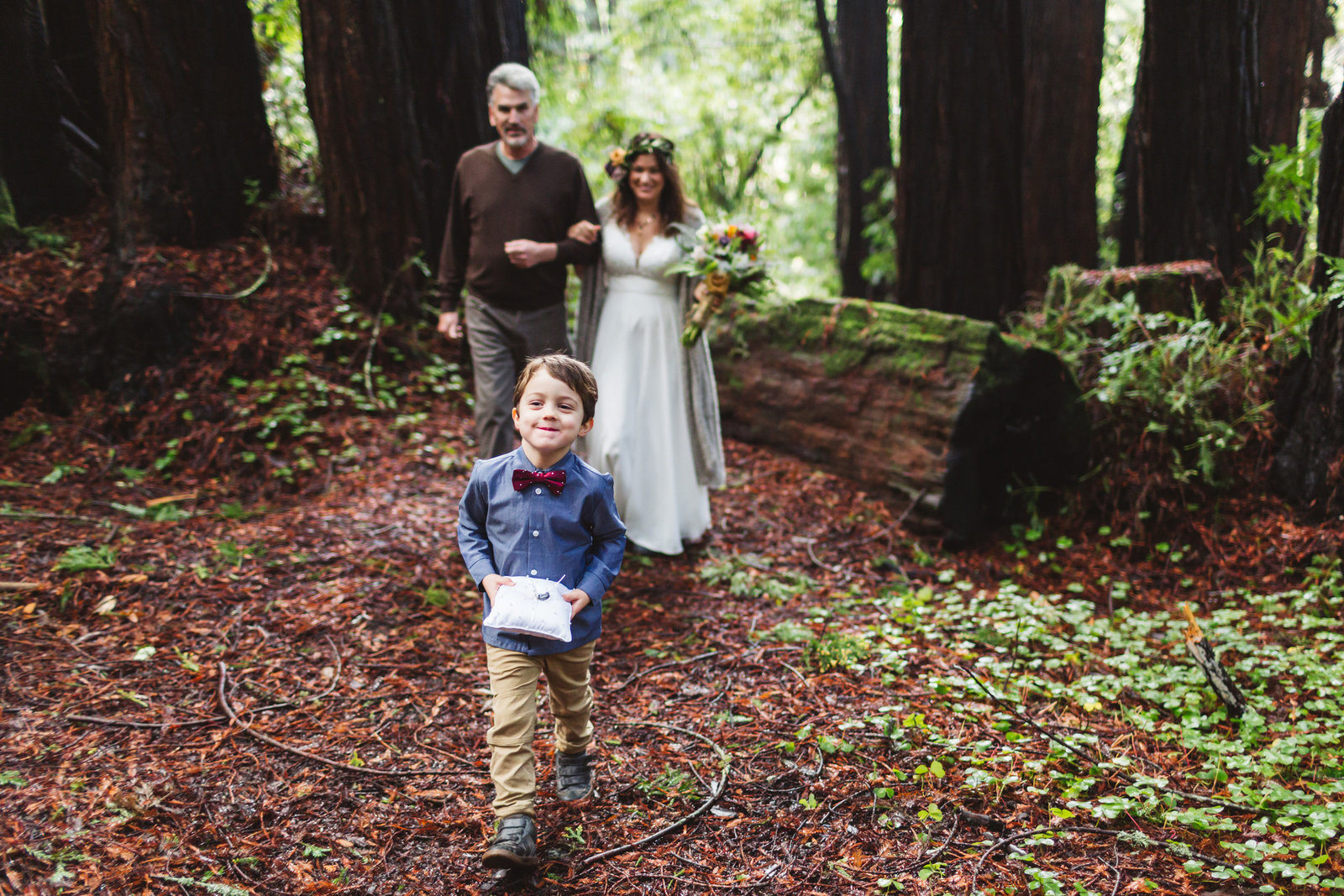 cute ring bearer leads bride and her father down the redwood aisle