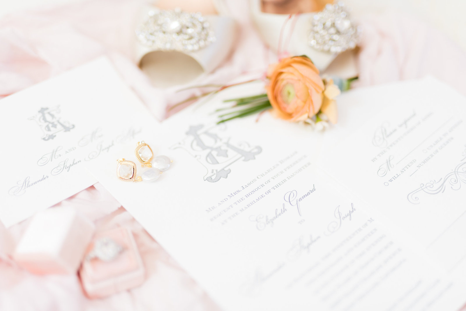 Earrings sit on Blush and White Invitation Suite.