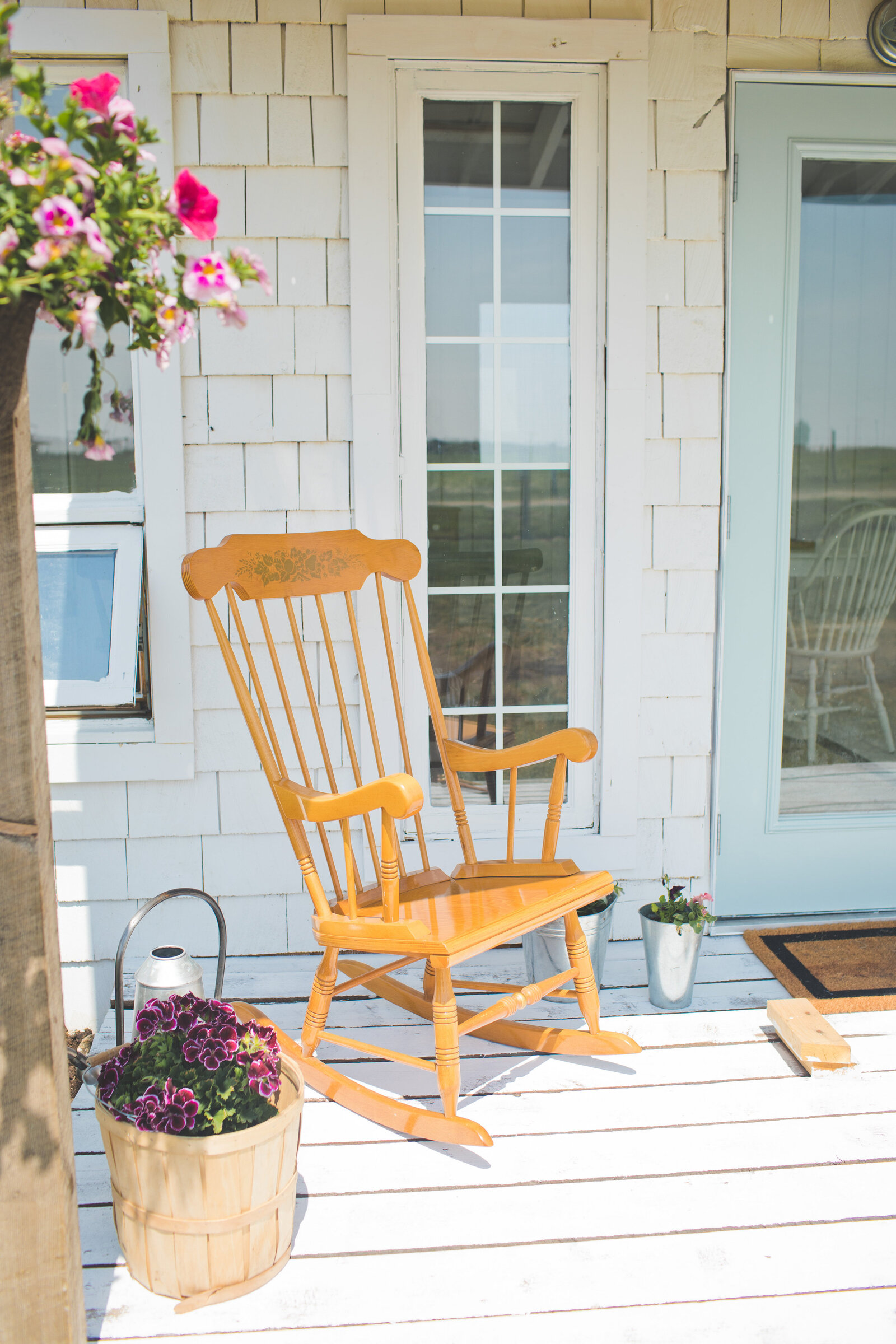 white cottage with a rocking chair on porch