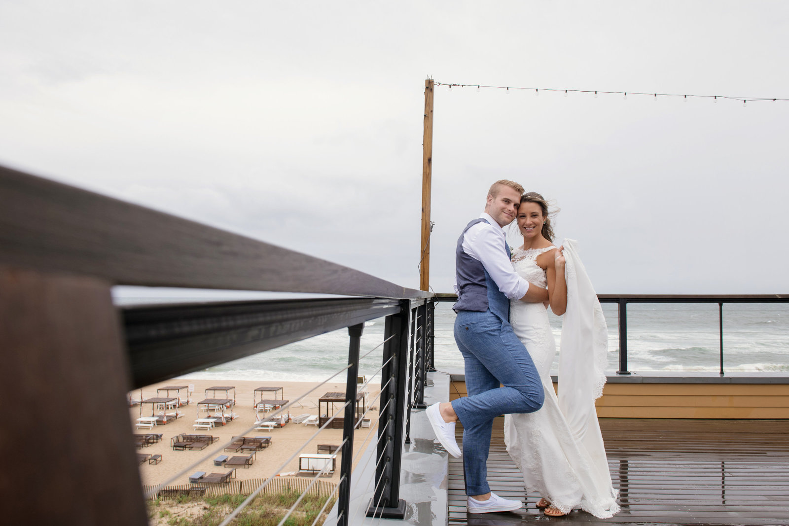 groom holding his bride on the outside desk at Gurneys Montauk Resort wedding