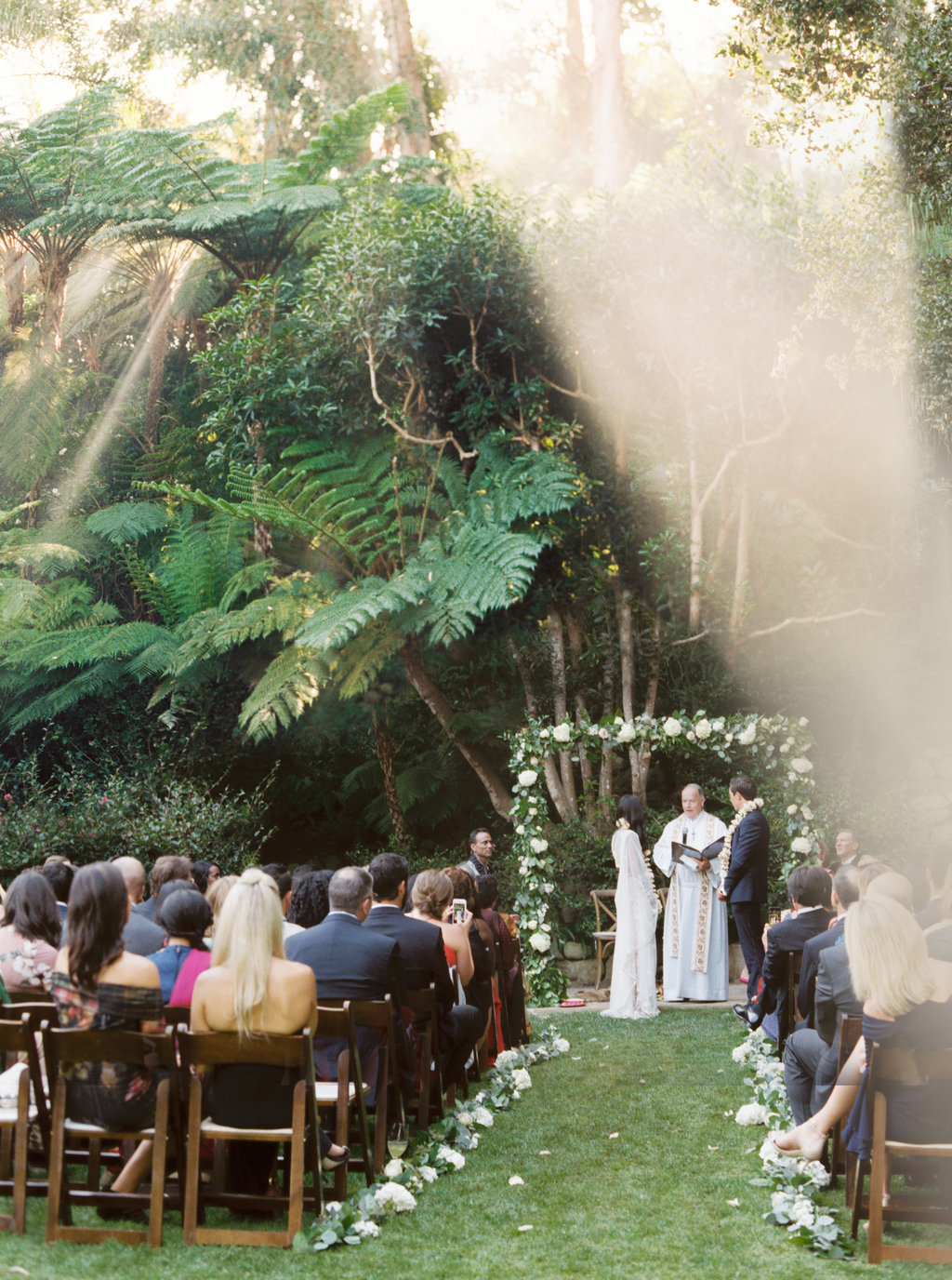 Indian and Christian wedding ceremony with white floral arch at Butterfly Lane Estate in Montecito
