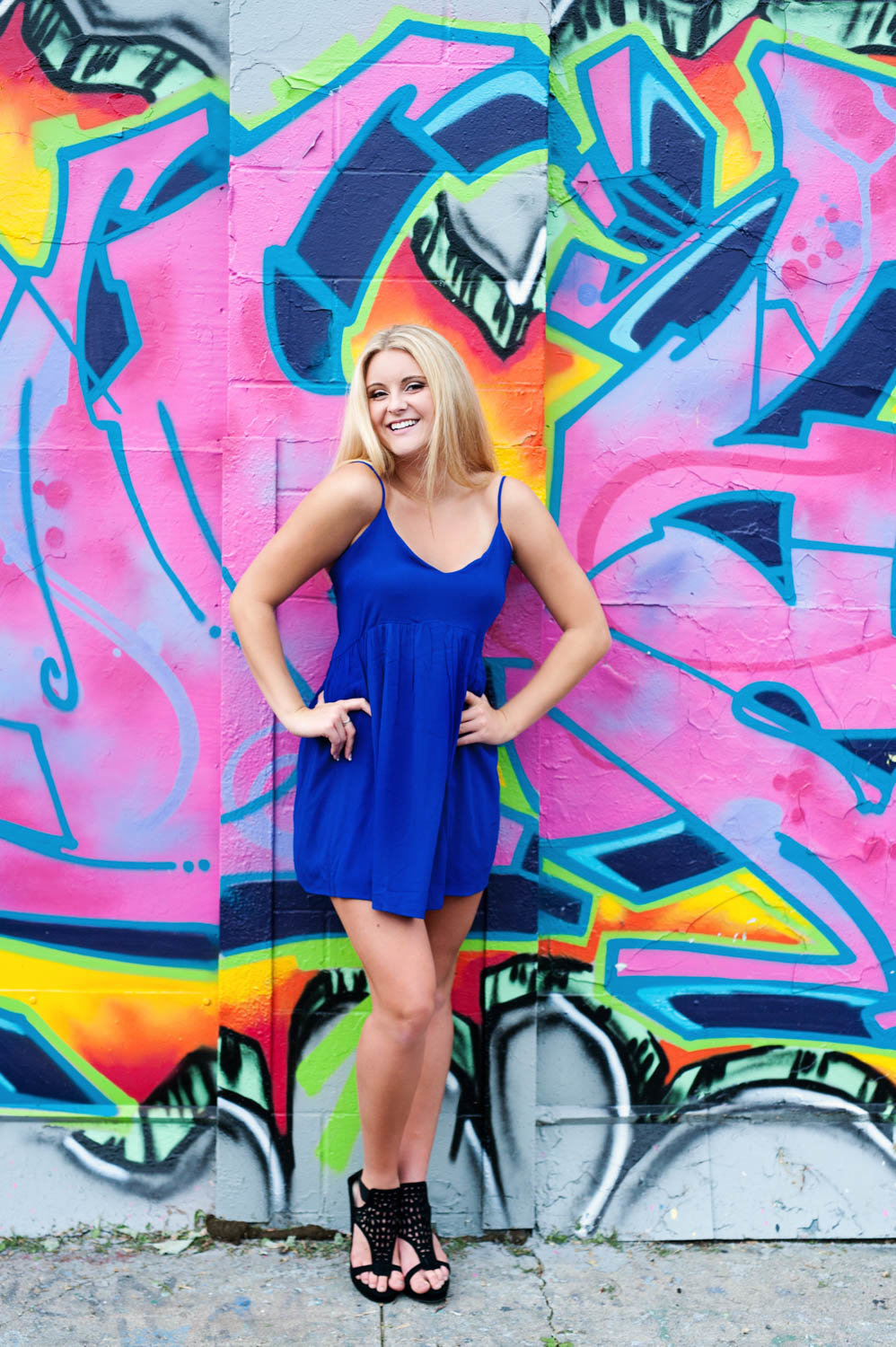 Senior picture of blonde girl in front of graffiti wall