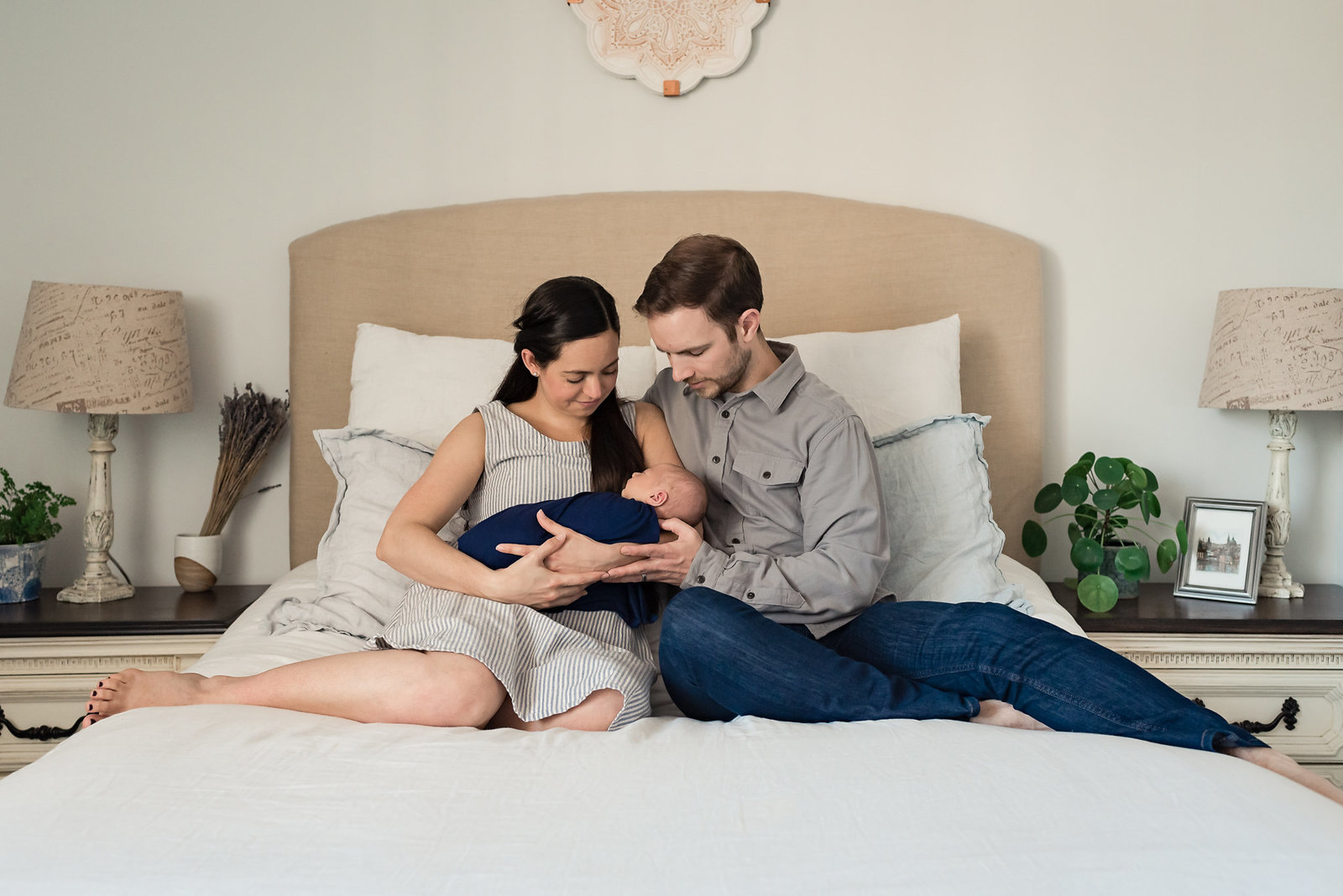 Mom and dad on bed with newborn during Los Angles Newborn Pictures