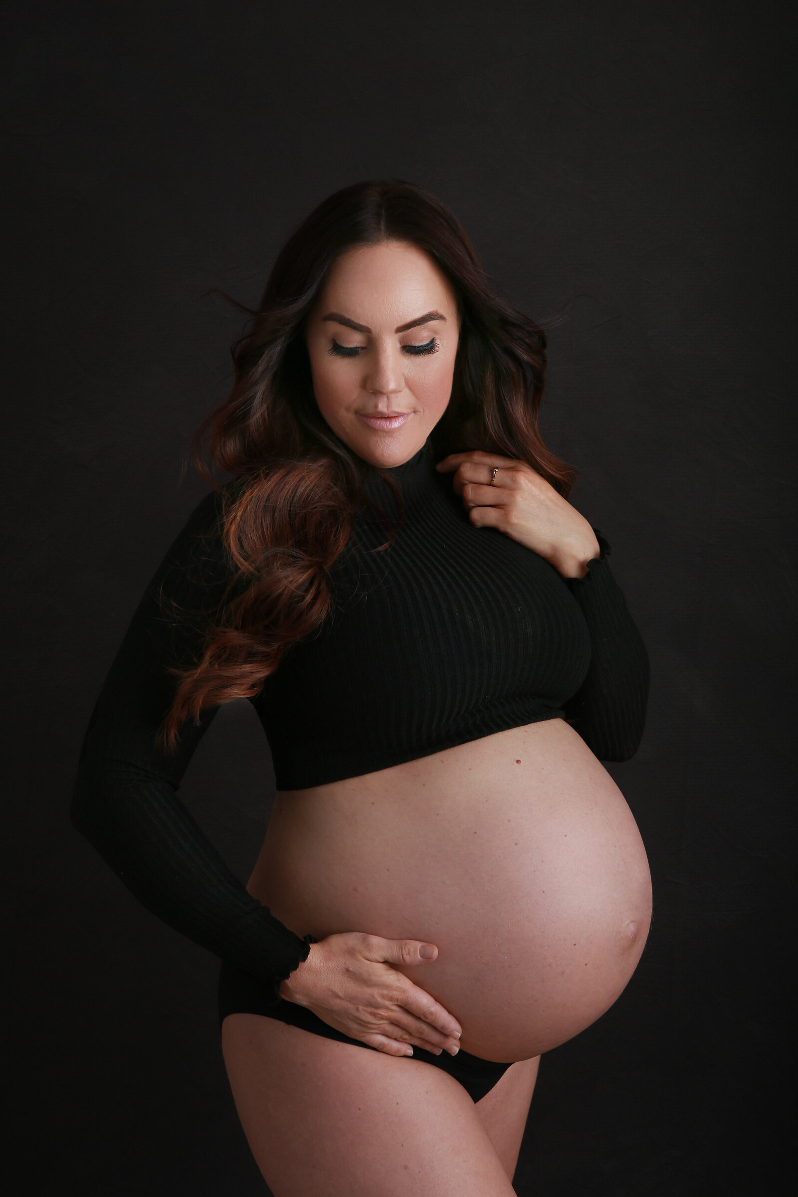 Professional maternity portrait in-studio, brunette pregnant lady holding belly