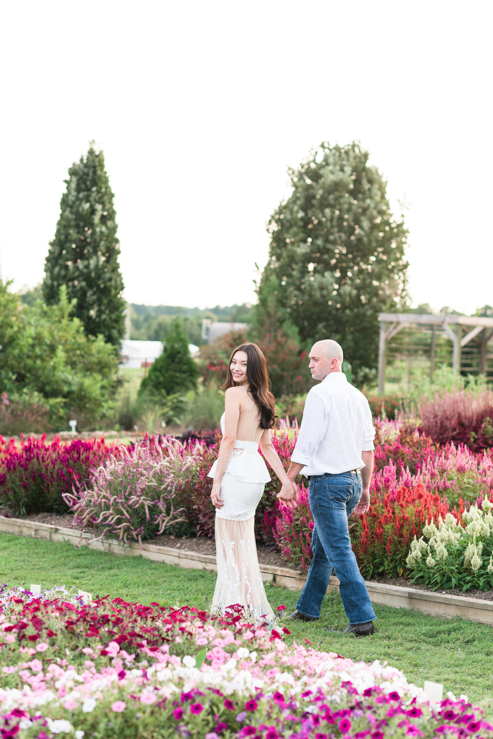 bride and groom walking in a flower garden at JC Raulston Arboretum with the bride looking back at the camera