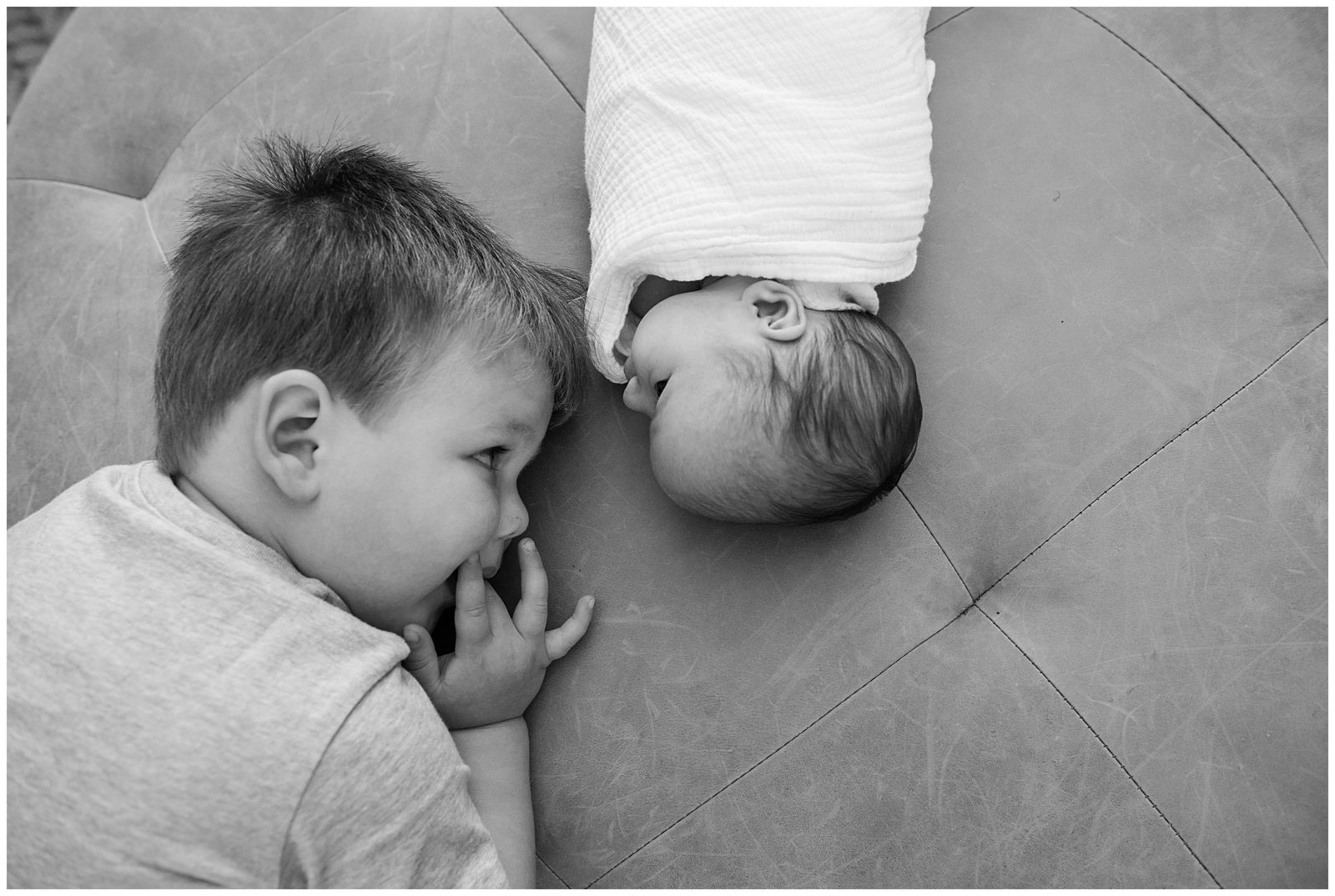 Black and white photo of baby girl and big brother looking at each other Emily Ann Photography Seattle Photographer