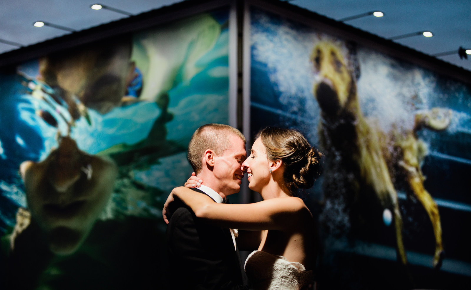 a downtown Columbus wedding photo taken at night of a couple in front of a colorful billboard with a dog and swimmer underwater