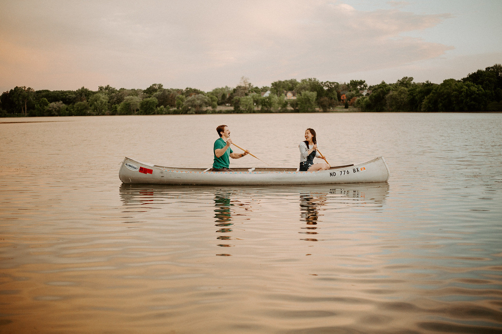 Couple canoeing in a minnesota lake at sunset during their engagement session