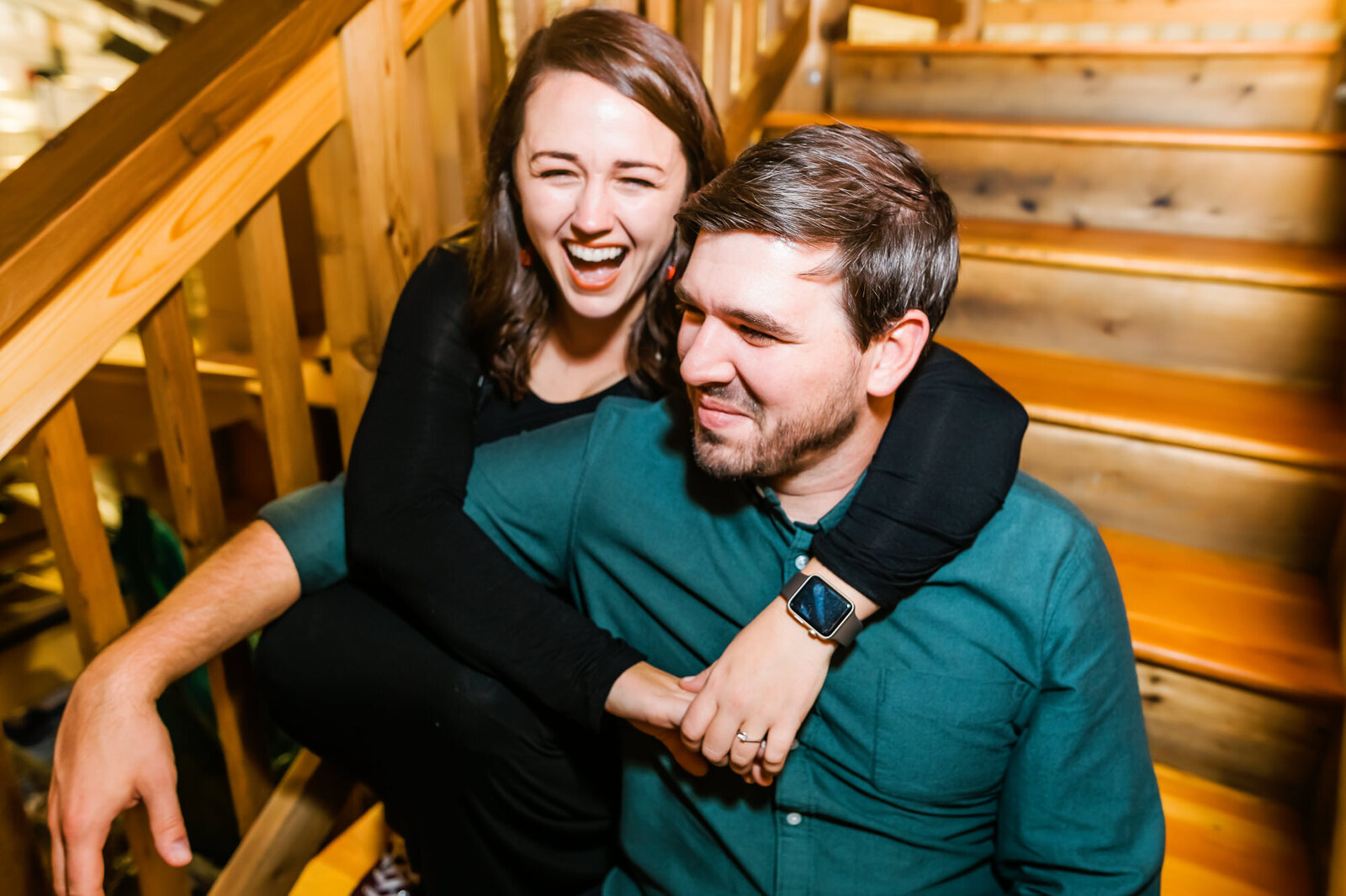 Candid engagement photo of a couple sitting together and laughing at Civil Life Brewery in St. Louis
