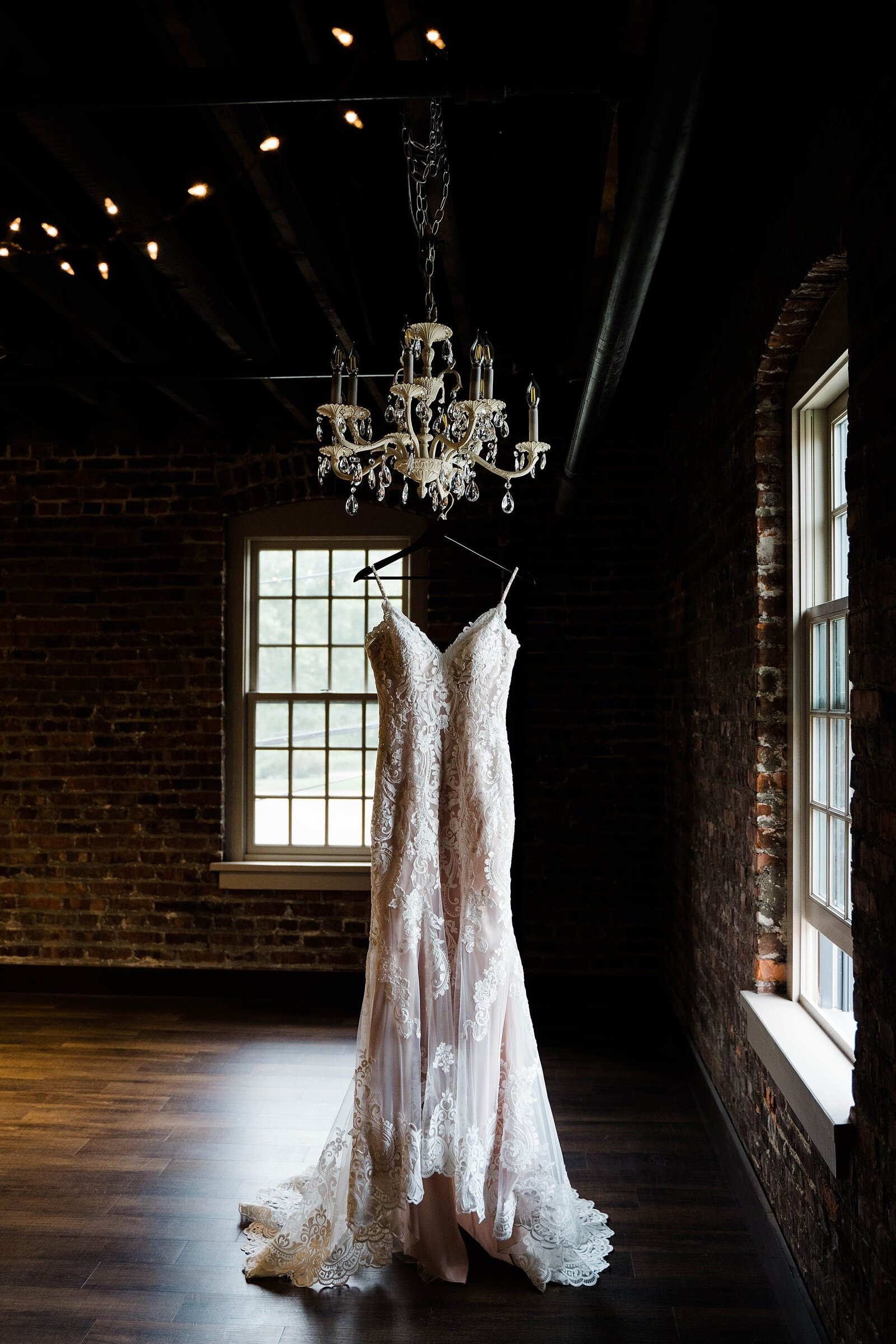Bride's dress hangs from chandellier at The Beck