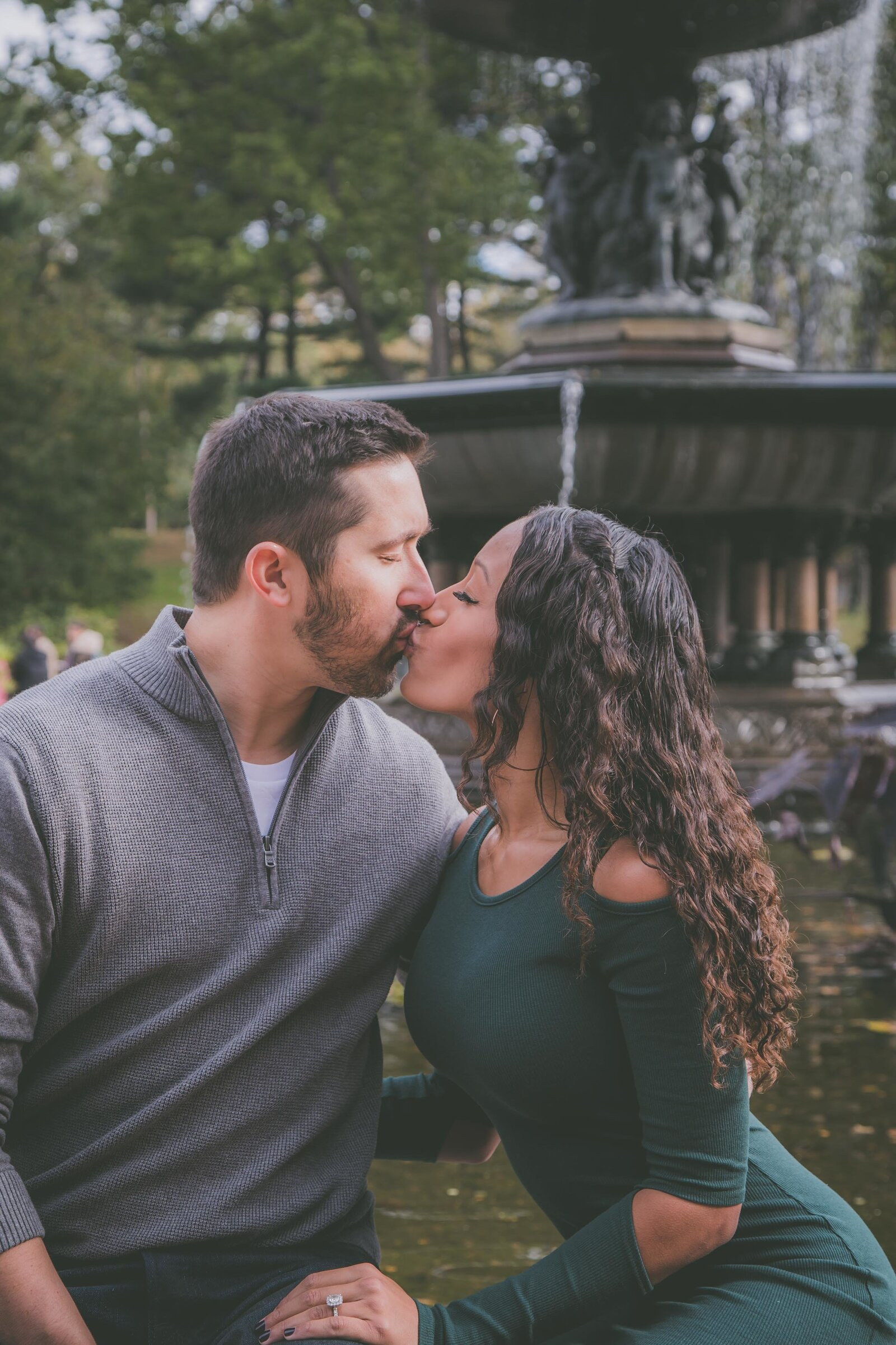 Couple sits and kisses in front of Central Park fountain.