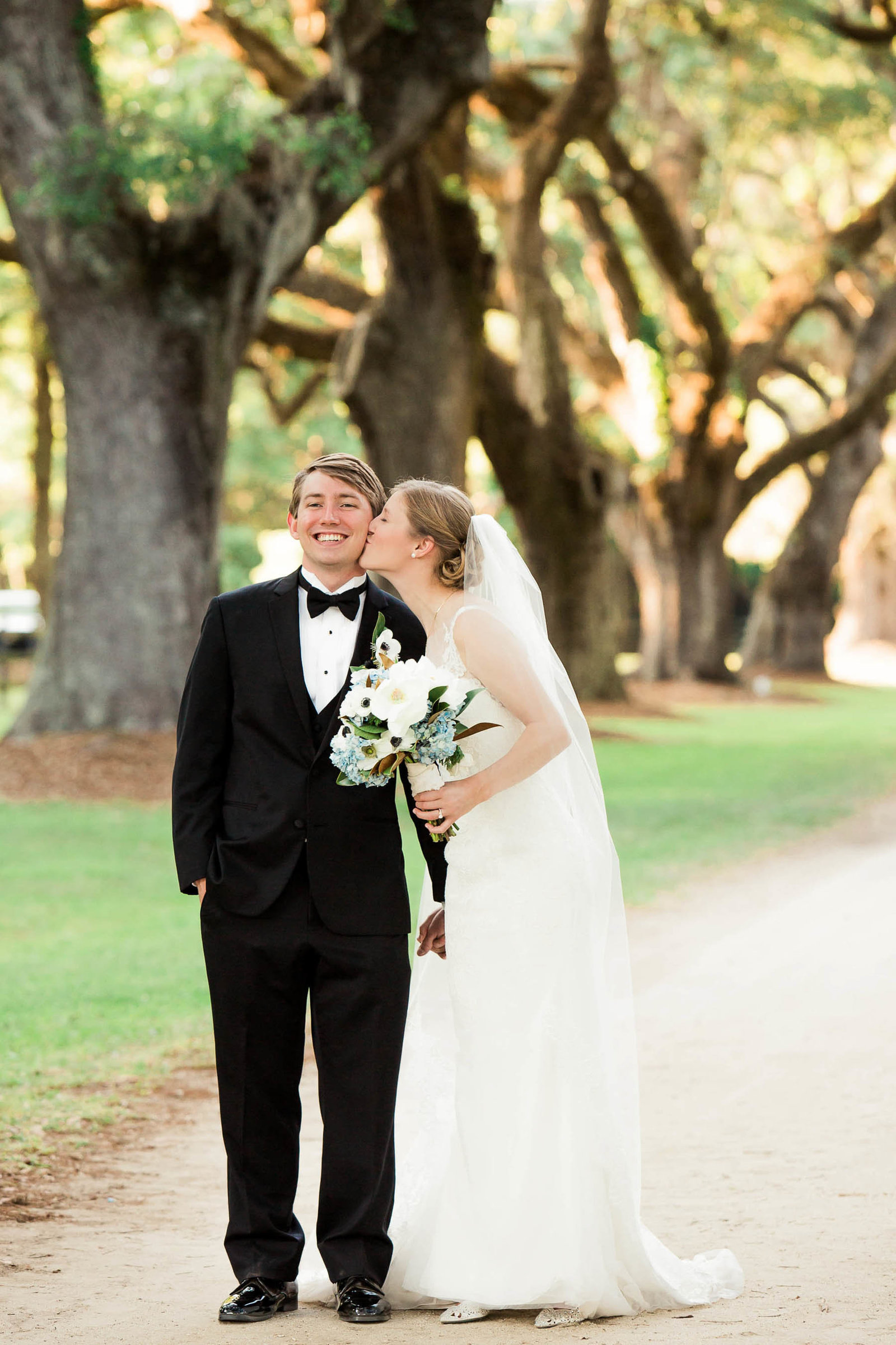Bride and groom stand under avenue of oaks, Oakland Plantation, Mt Pleasant, South Carolina