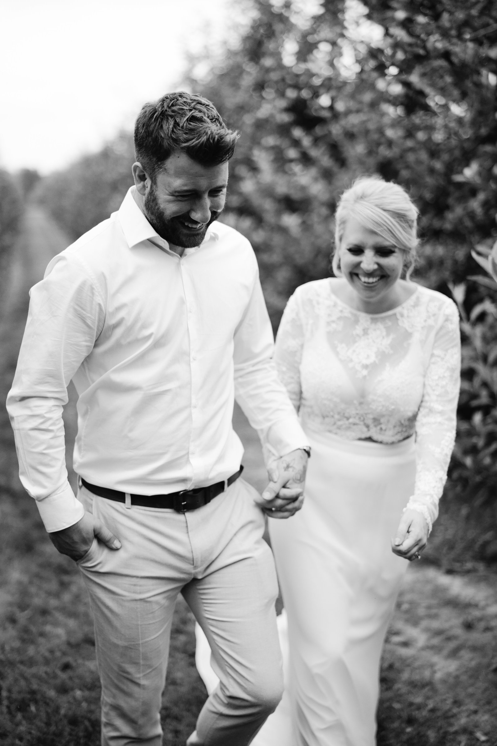 Black and white photograph of happy couple walking through an orchard
