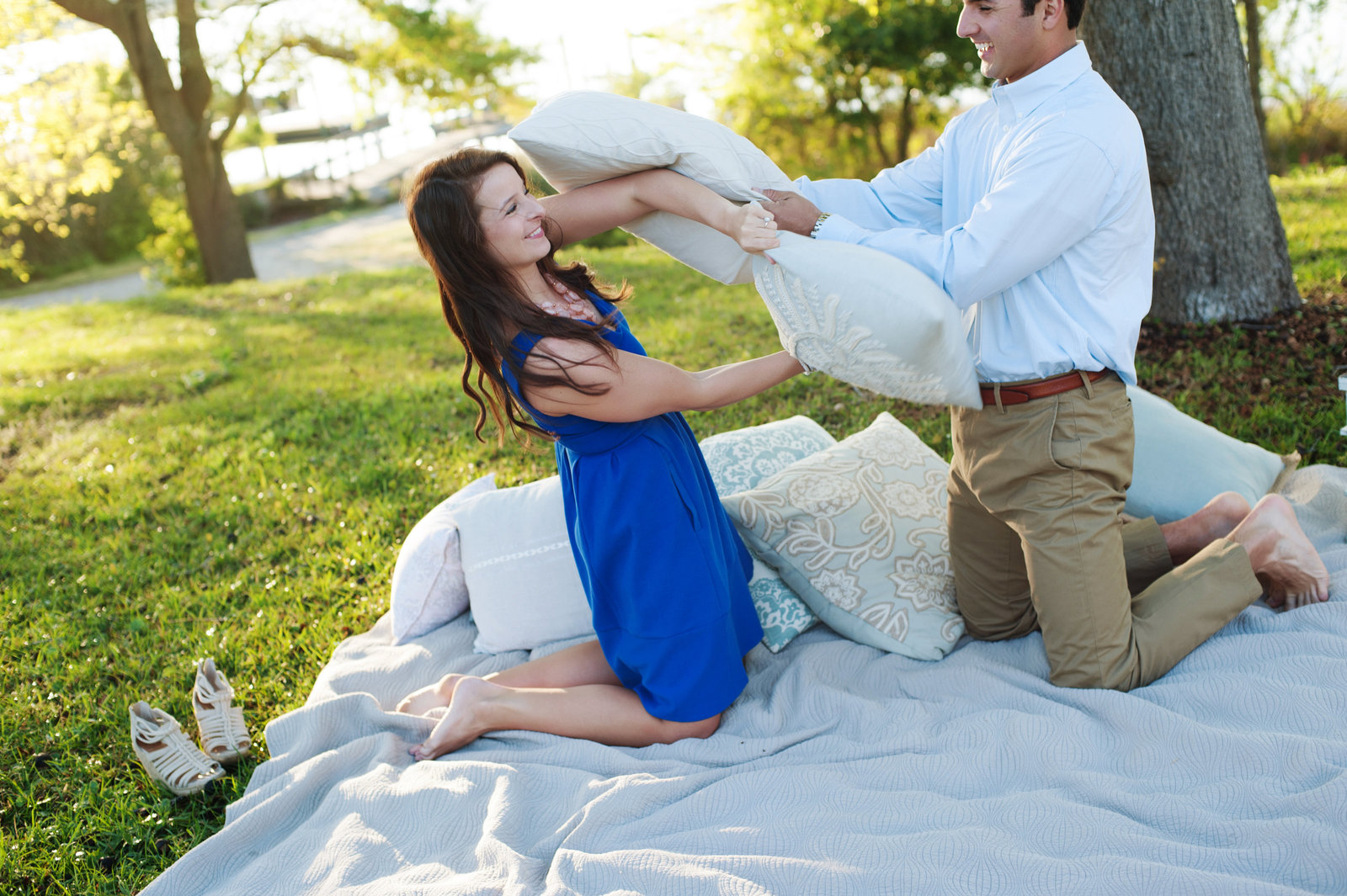 an engaged couple have a pillow fight on a blanket in the grass