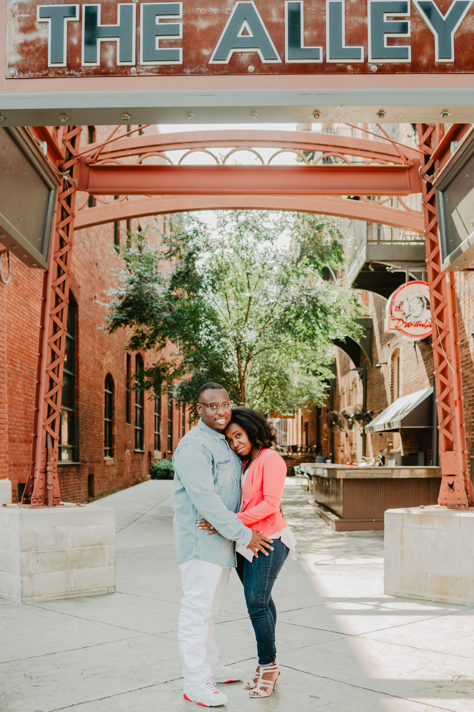 With the water tower above them atThe Alley, engaged couple looks directly at the camera with warm smiles