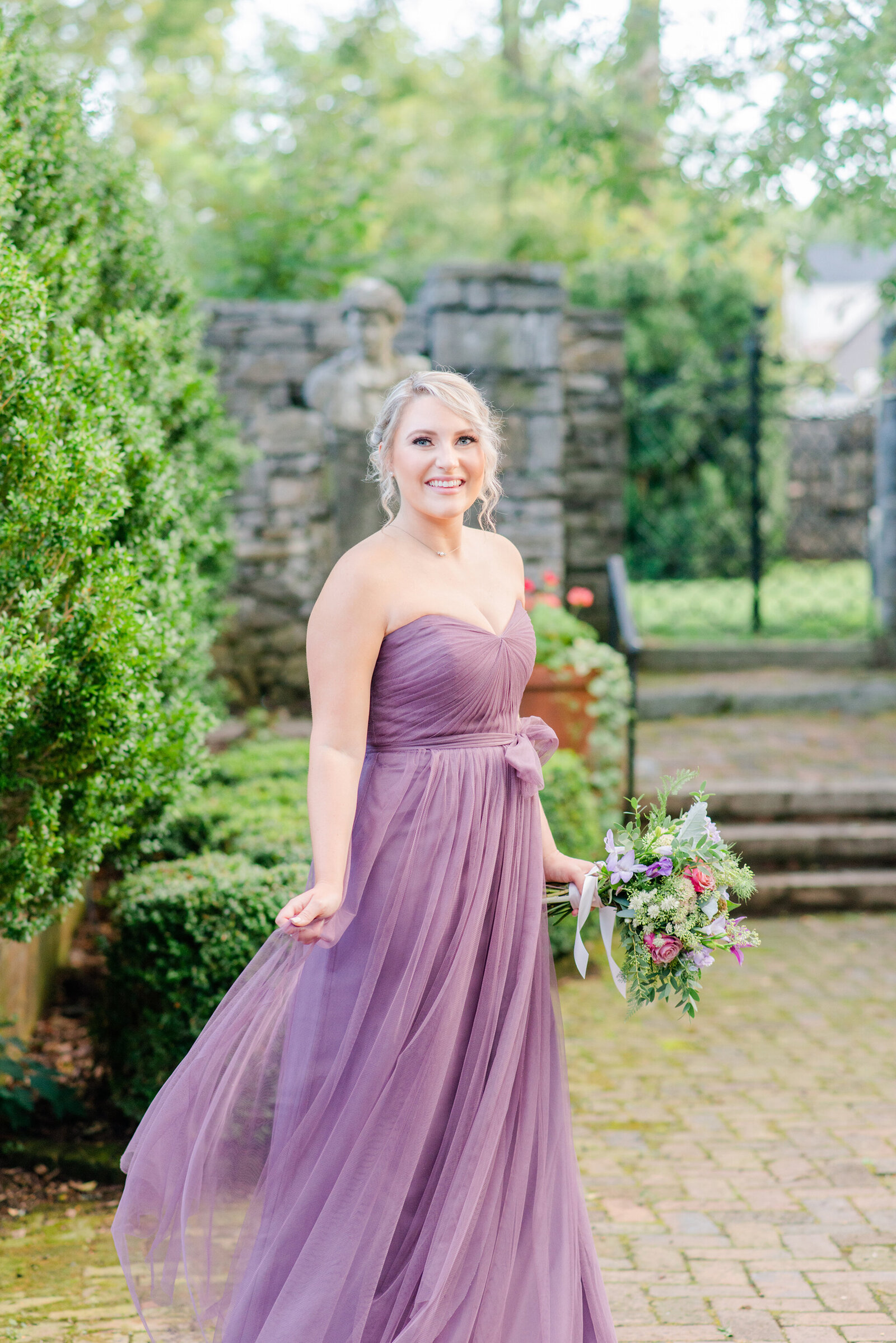Bridesmaid in purple gown holding flowers and smiling