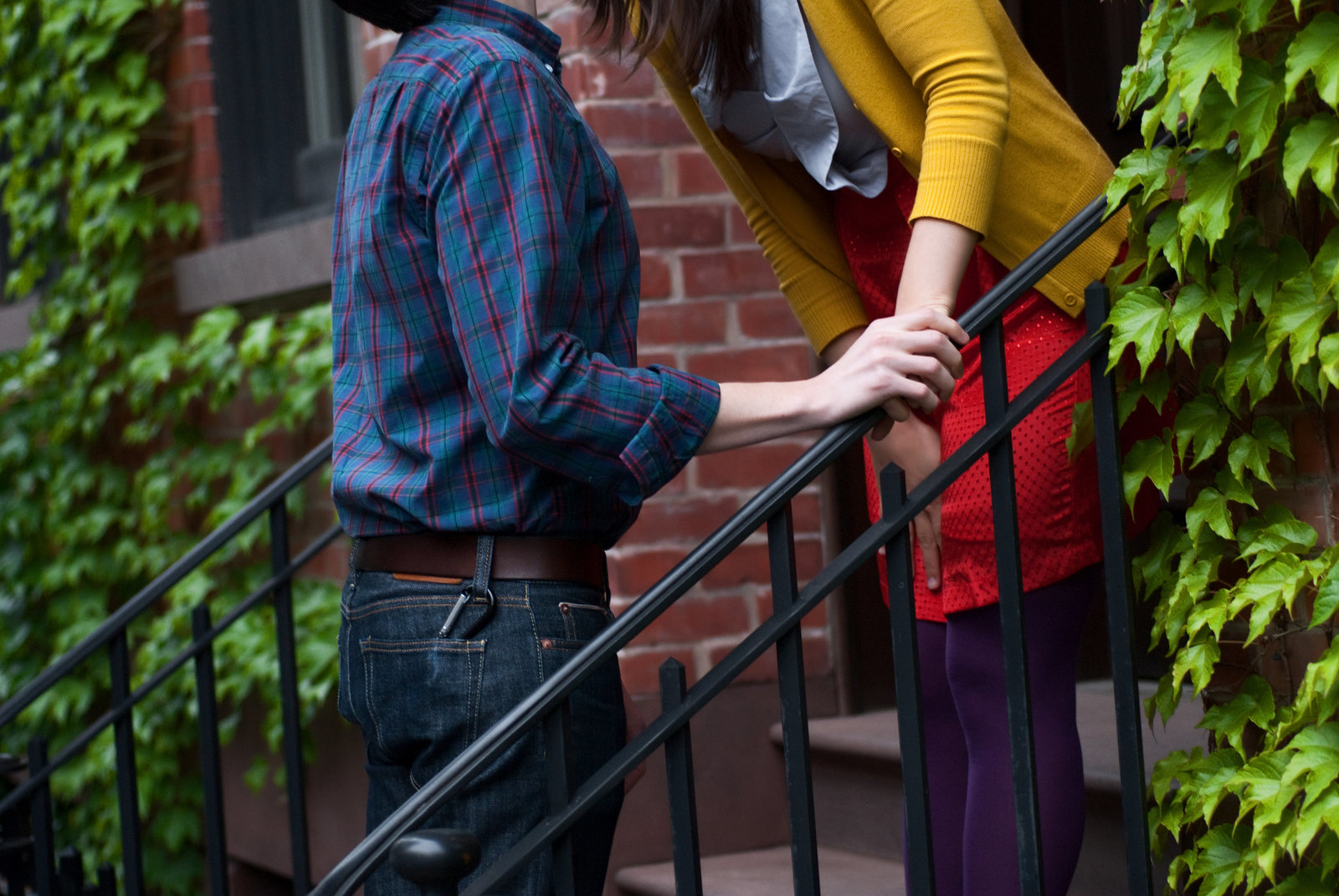 a couple wearing colorful clothes give a goodbye kiss on a nyc apartment stoop