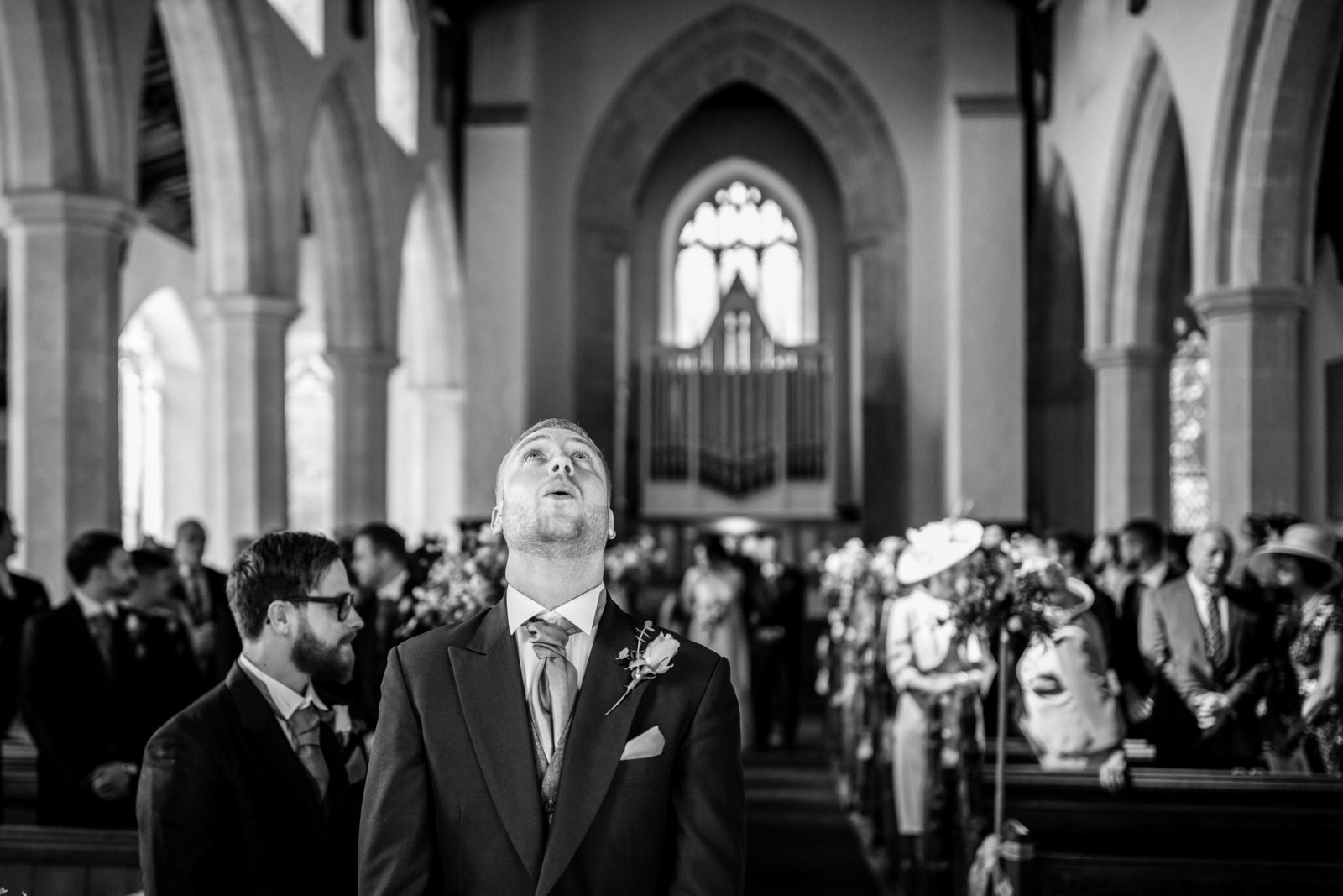 A groom takes a deep breathe and looks up whilst his Bride walks down the aisle at a Church in Norfolk.