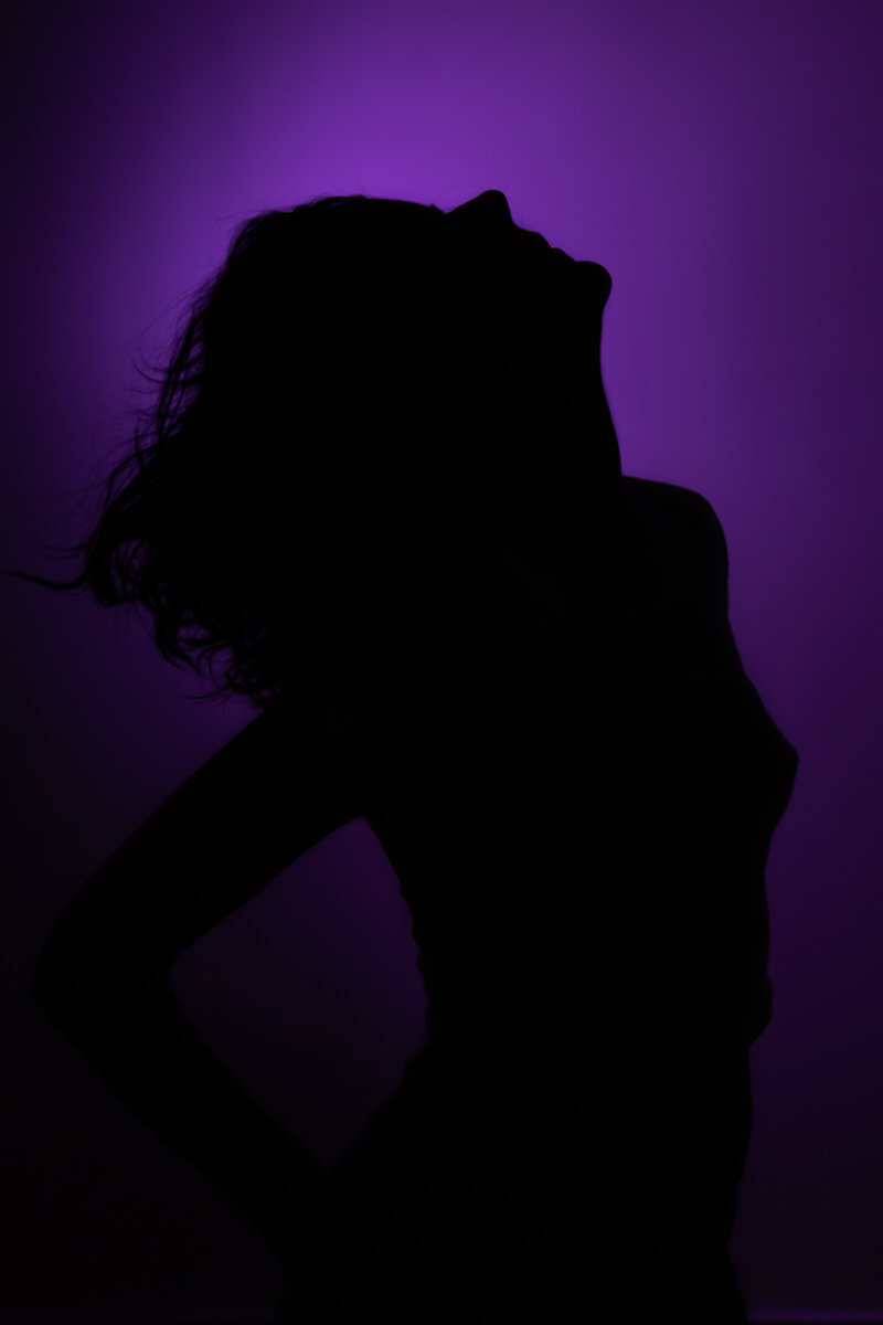 Boudoir silhouette photo of a woman with purple lights
