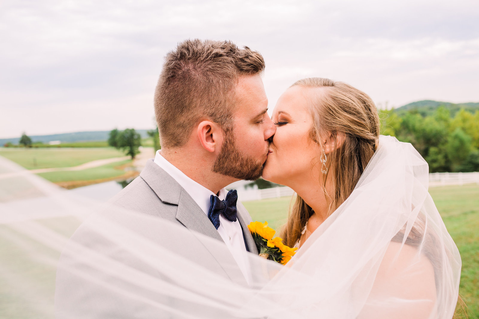 Bride and Groom, Whitney and Derik, embrace in a kiss as Whitney's veil is swept by the wind at Chaumette Winery.