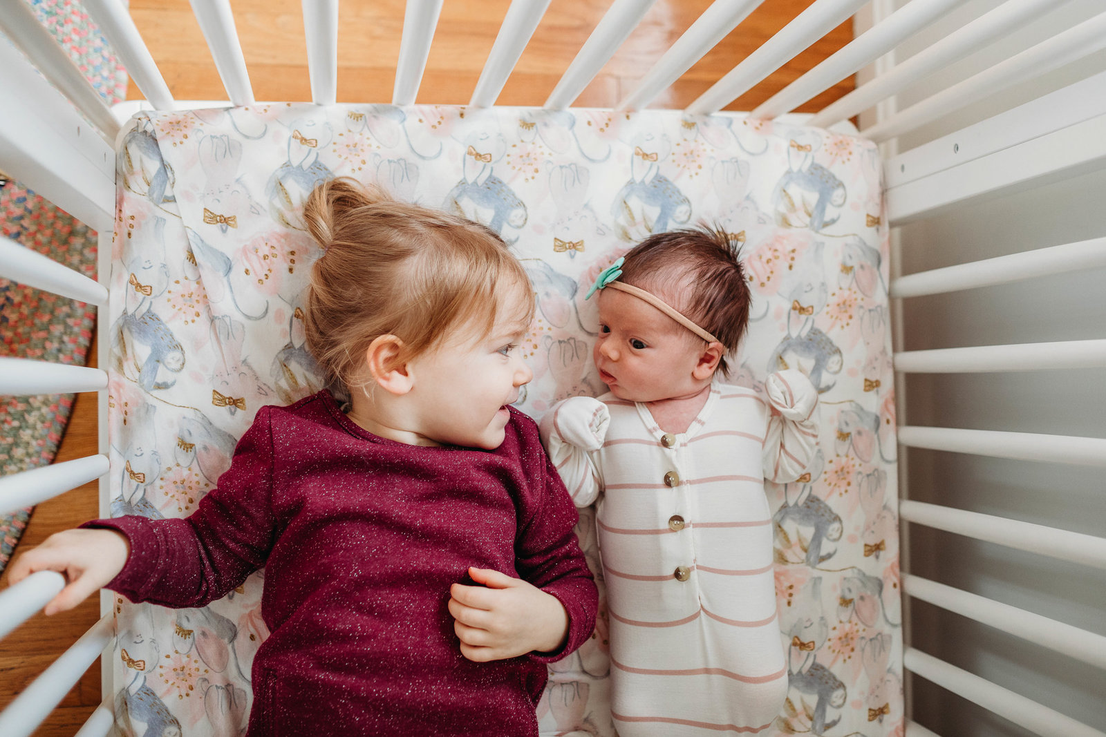 big and little sister look at each other in crib during cohasset newborn session