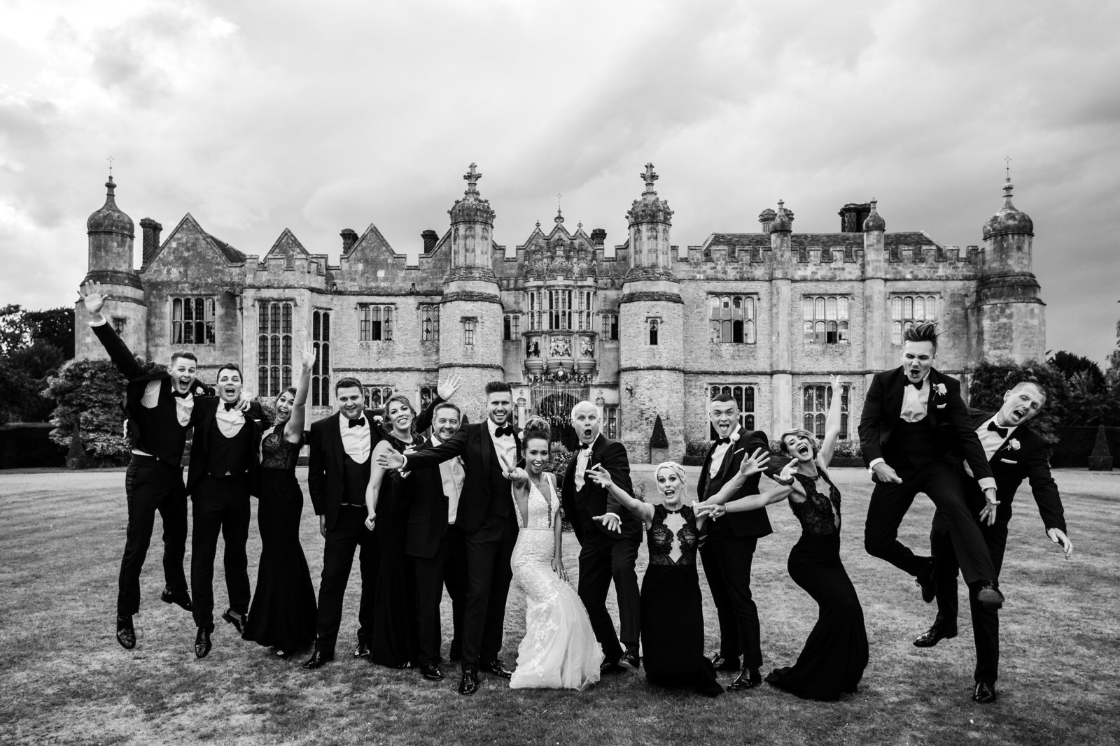 The wedding party line up and jump with enthusiasm in front of Hengrave Hall. The bridesmaids are wearing black dresses and the groomsmen in black tie.