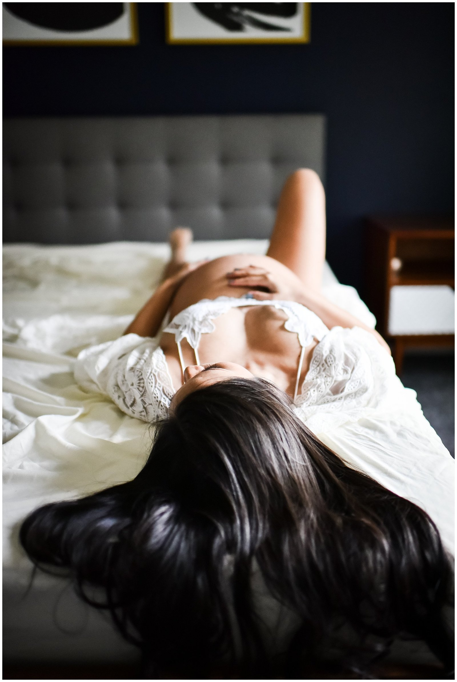 Pregnant woman laying on bed holding belly wearing lace kimono robe Emily Ann Photography Seattle Photographer.