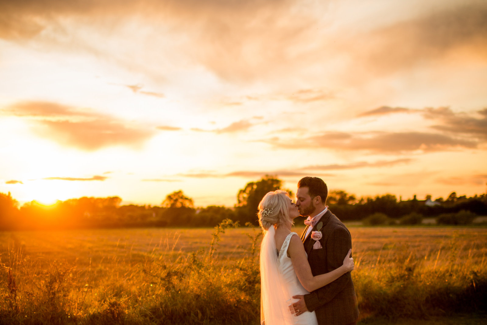 Bride and Groom stand in front of a Norfolk wheat field and kiss whilst the sun sets behind them.