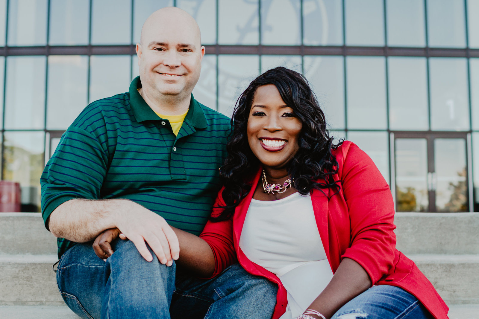 Engaged couple sitting on the steps in front of Bryant-Denny Stadium