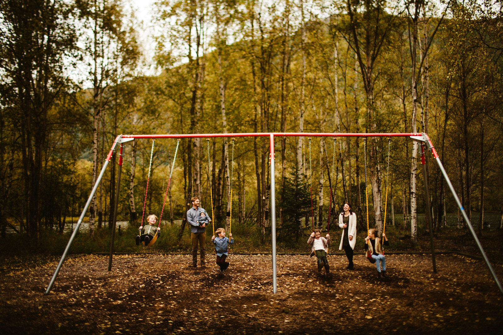 family with five children on a swing set in the fall