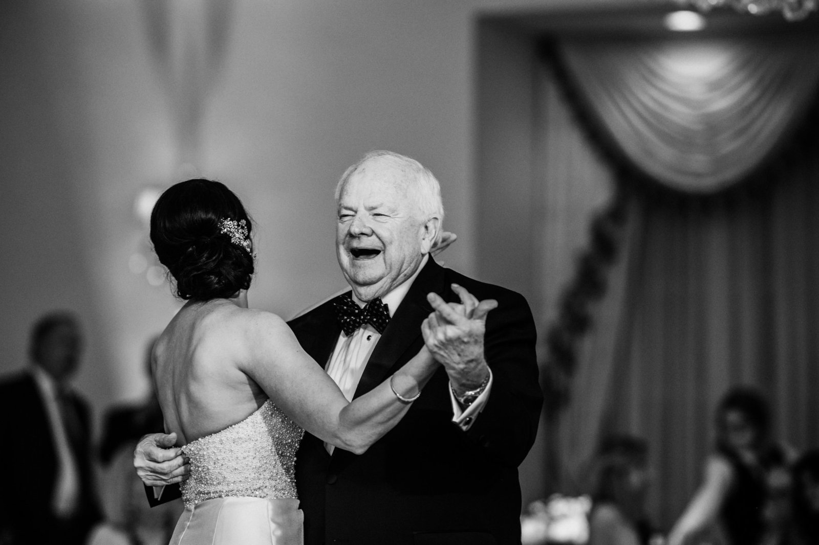 a fathers laughs and smiles while dancing with his daughter at her wedding