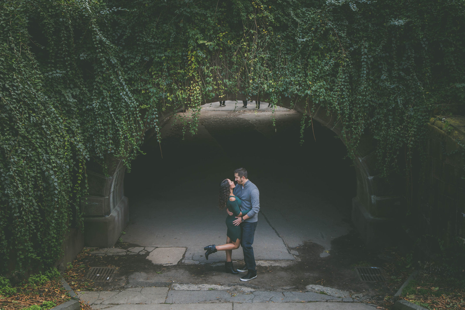 Couple stops by Central Park tunnel and kisses while she pops her foot.