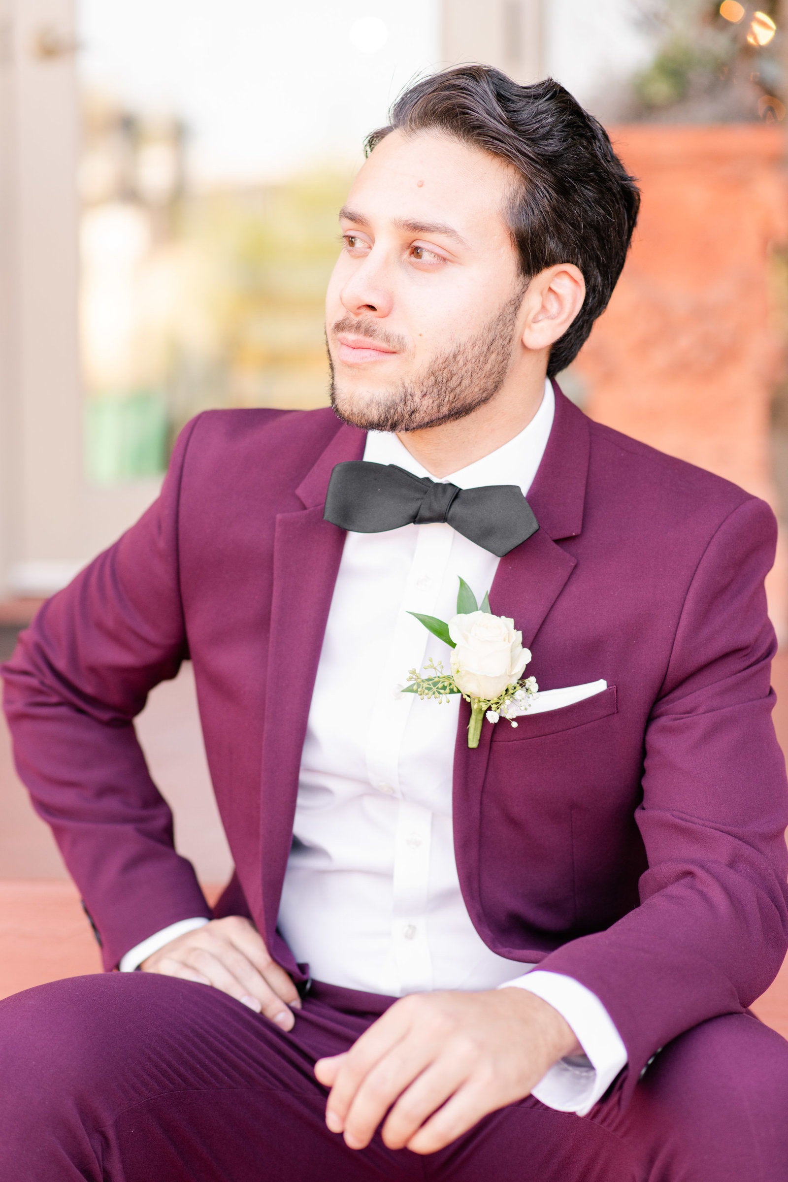 portrait of groom in maroon suit sitting on steps