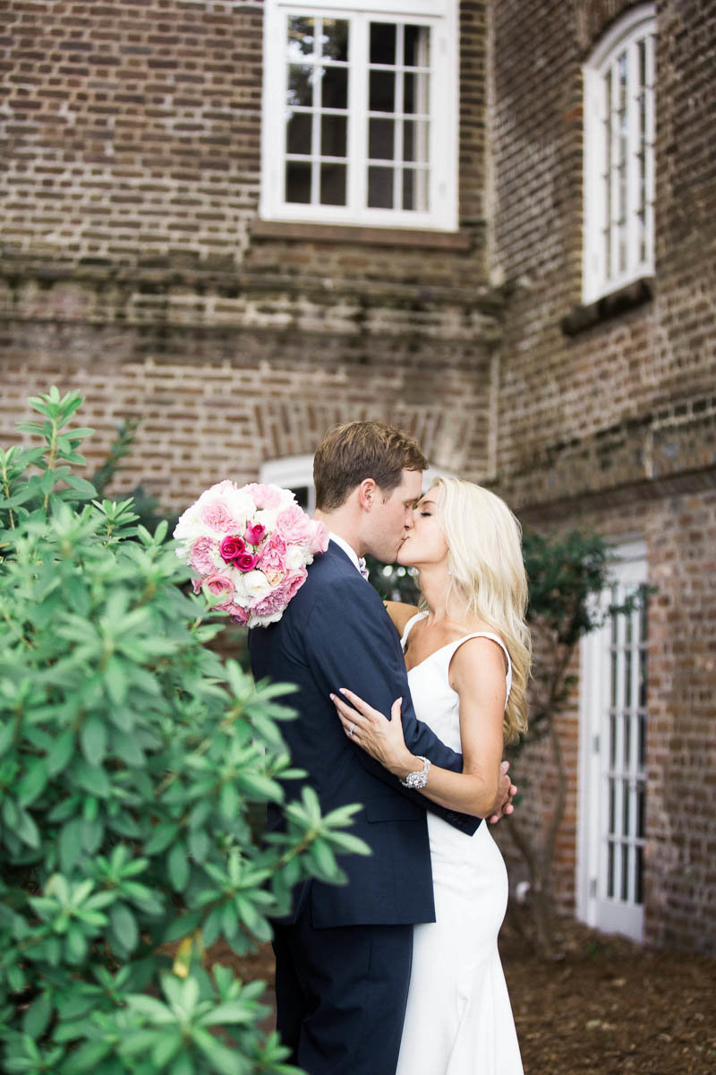 Bride and groom snuggle at the Rice Mill Building, Charleston, South Carolina. Kate Timbers Photography.