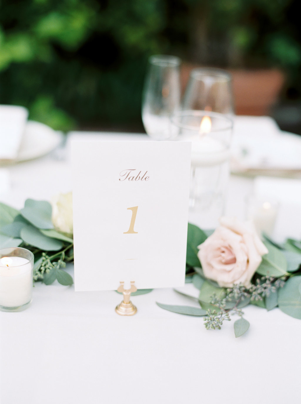 Wedding reception table setting with gold table numbers and pale pink floral centerpiece at Butterfly Lane Estate