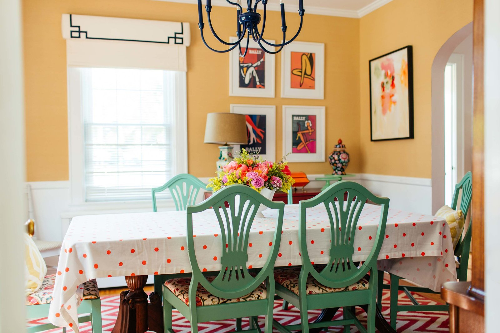 A yellow dining room with green chairs and chevron rug.