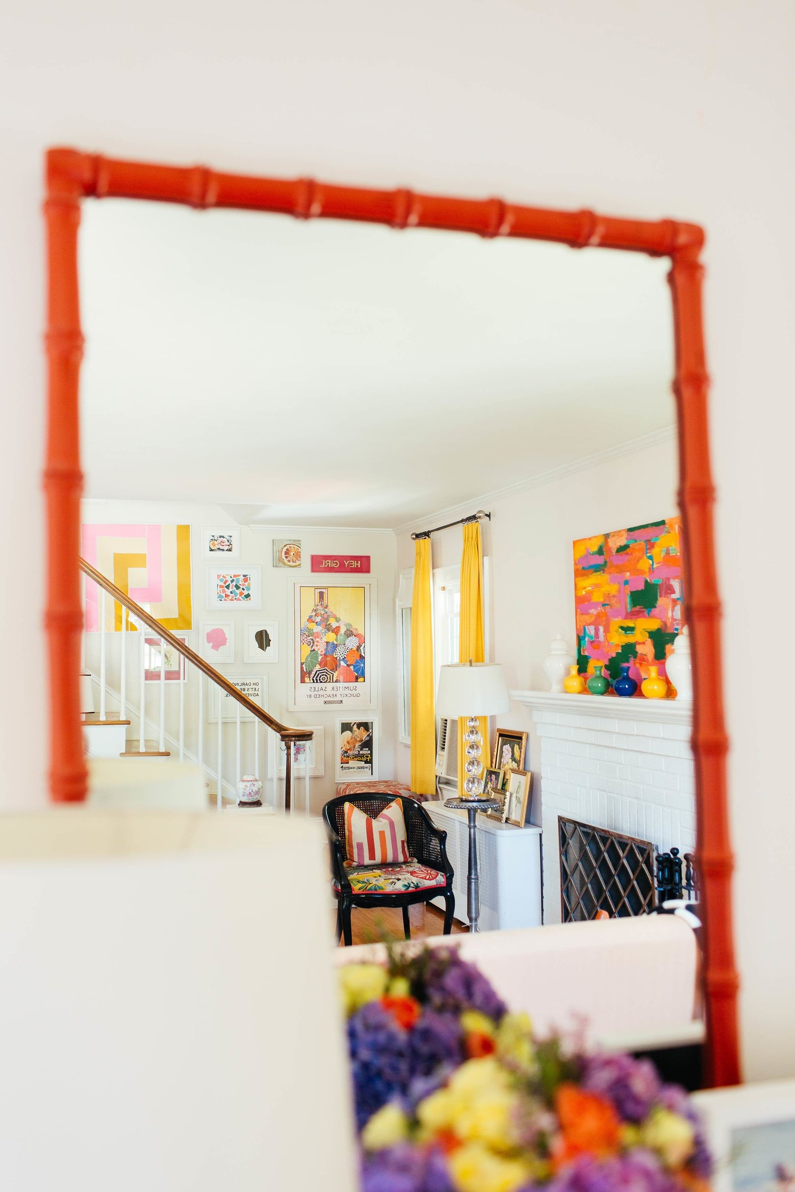 A dark orange framed mirror reflecting a colorful living room.