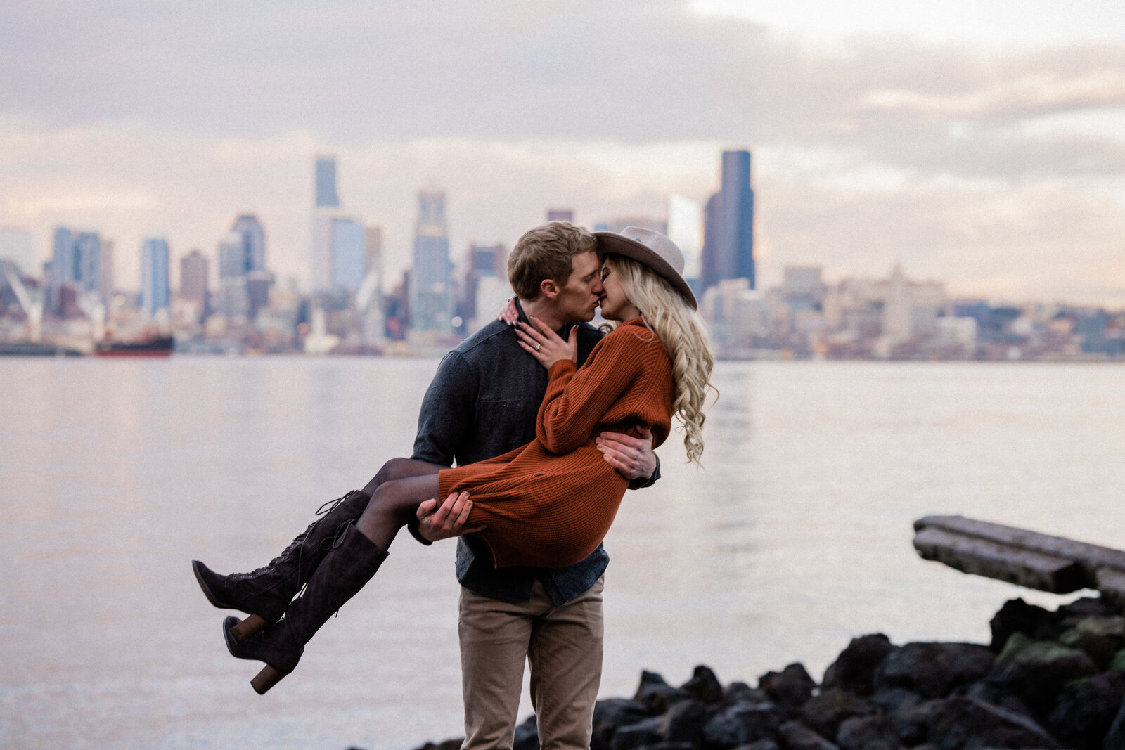 Man is holding woman in front of the Seattle skyline, one of the best spots to take engagement photos in Seattle