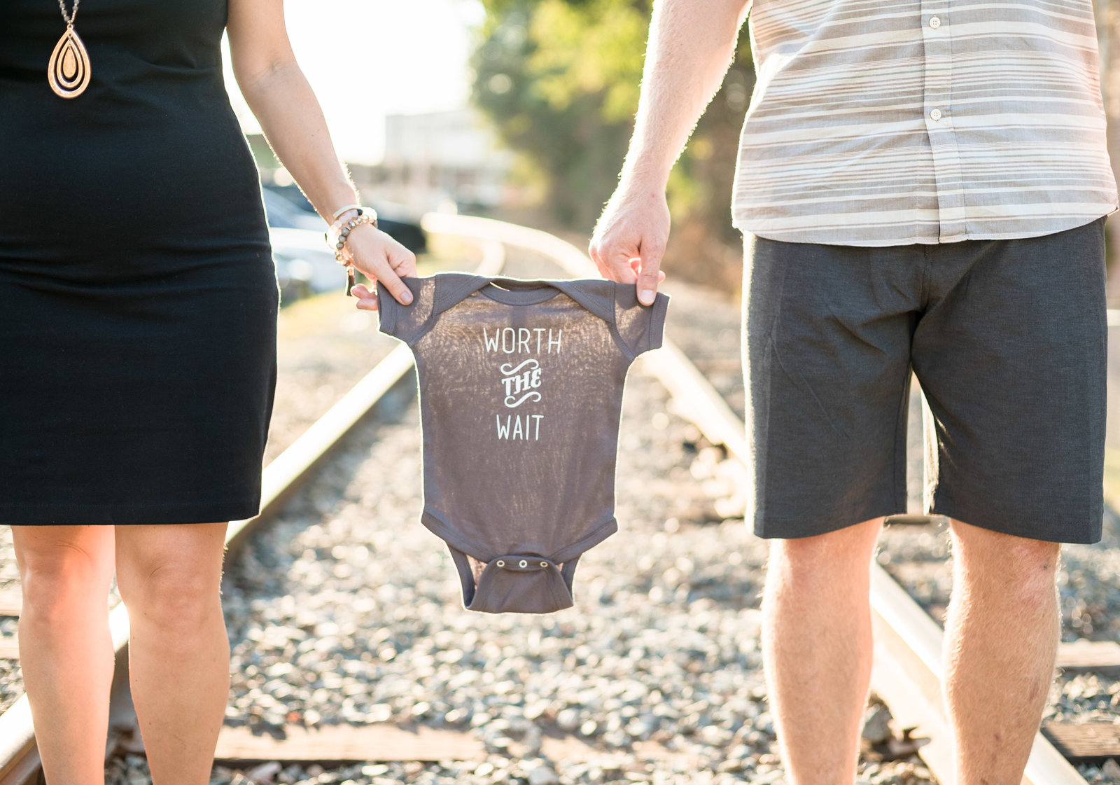 Charlotte Maternity photographer shot of couple on beach NODA railroad tracks