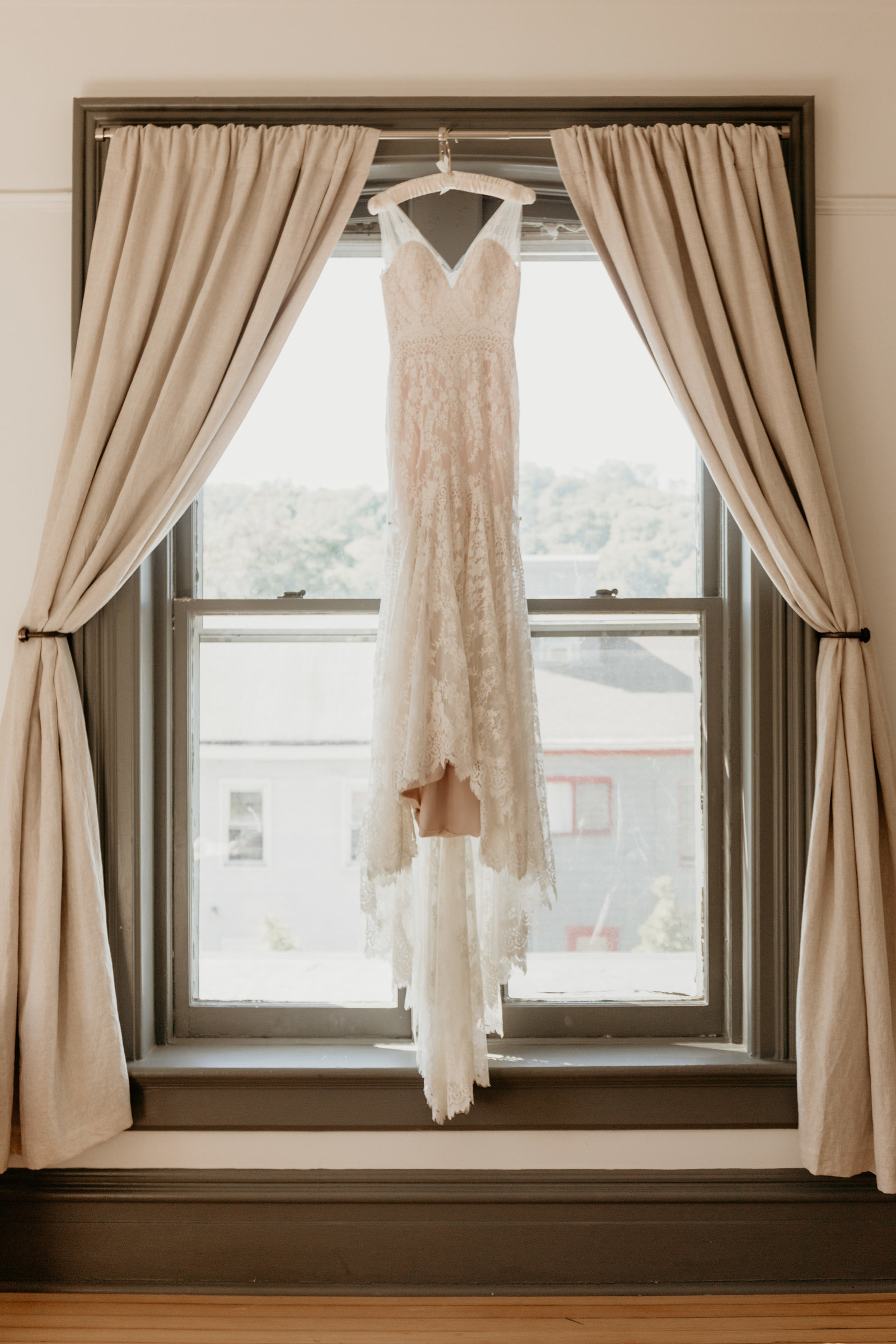 Wedding dress hanging in a natural light window.