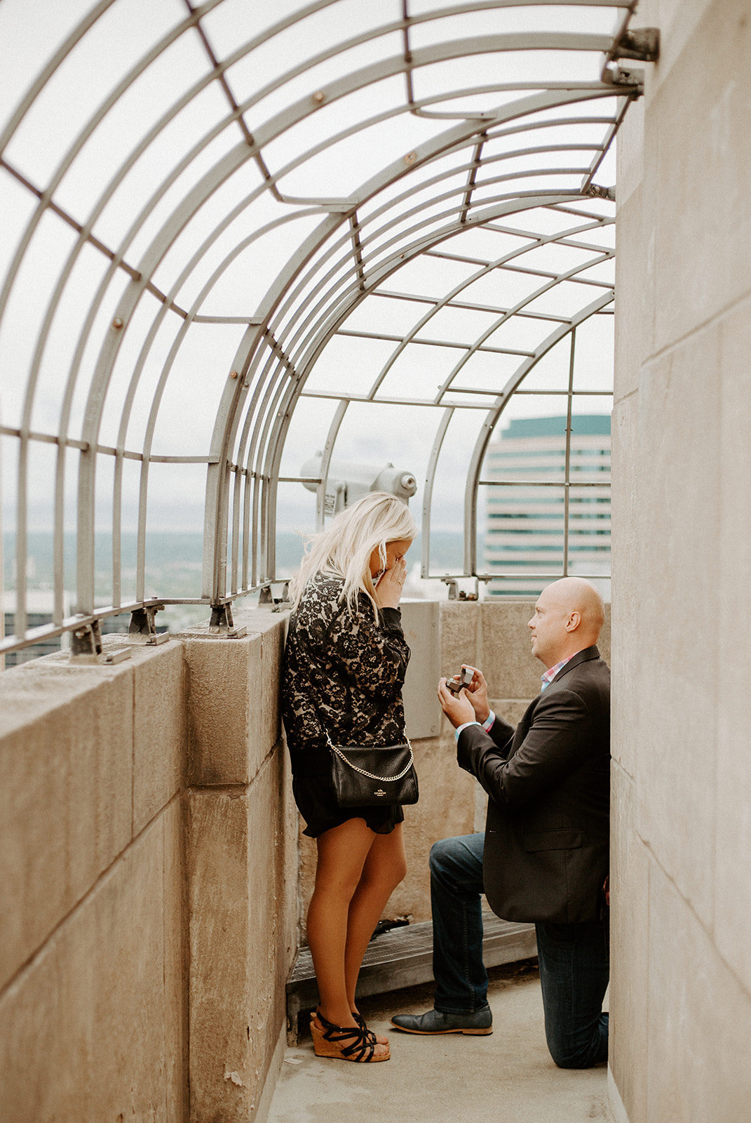 Man proposing to his girlfriend on one knee at the top of the Foshay building in Minneapolis