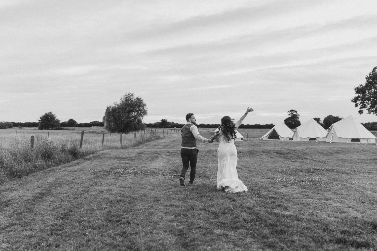 Black and white photograph of Helen Anderson's wedding day running away in to the distance cheering with tipi in the background at Godwick Hall