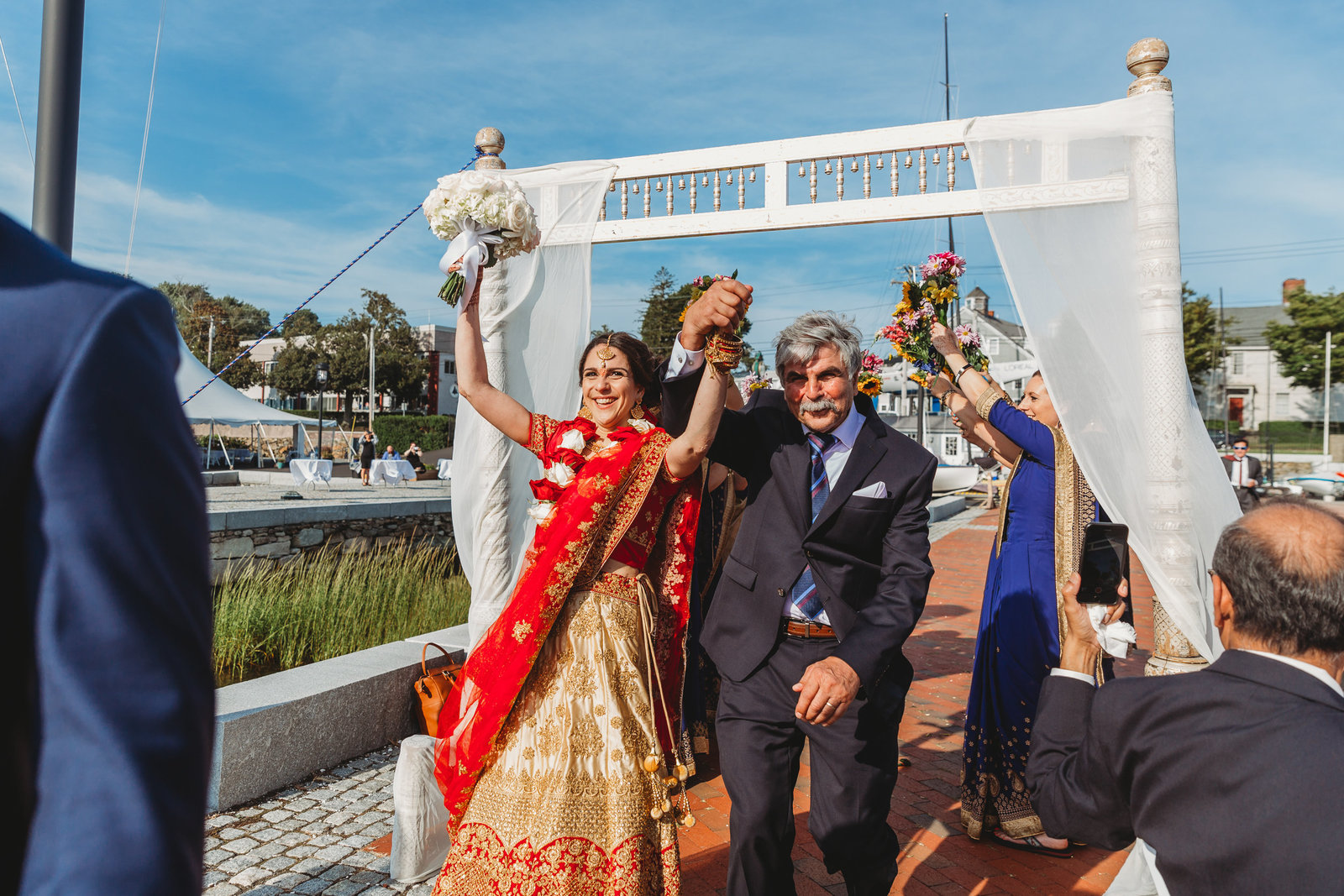 indian bride and father walk under archway into celebration in mass