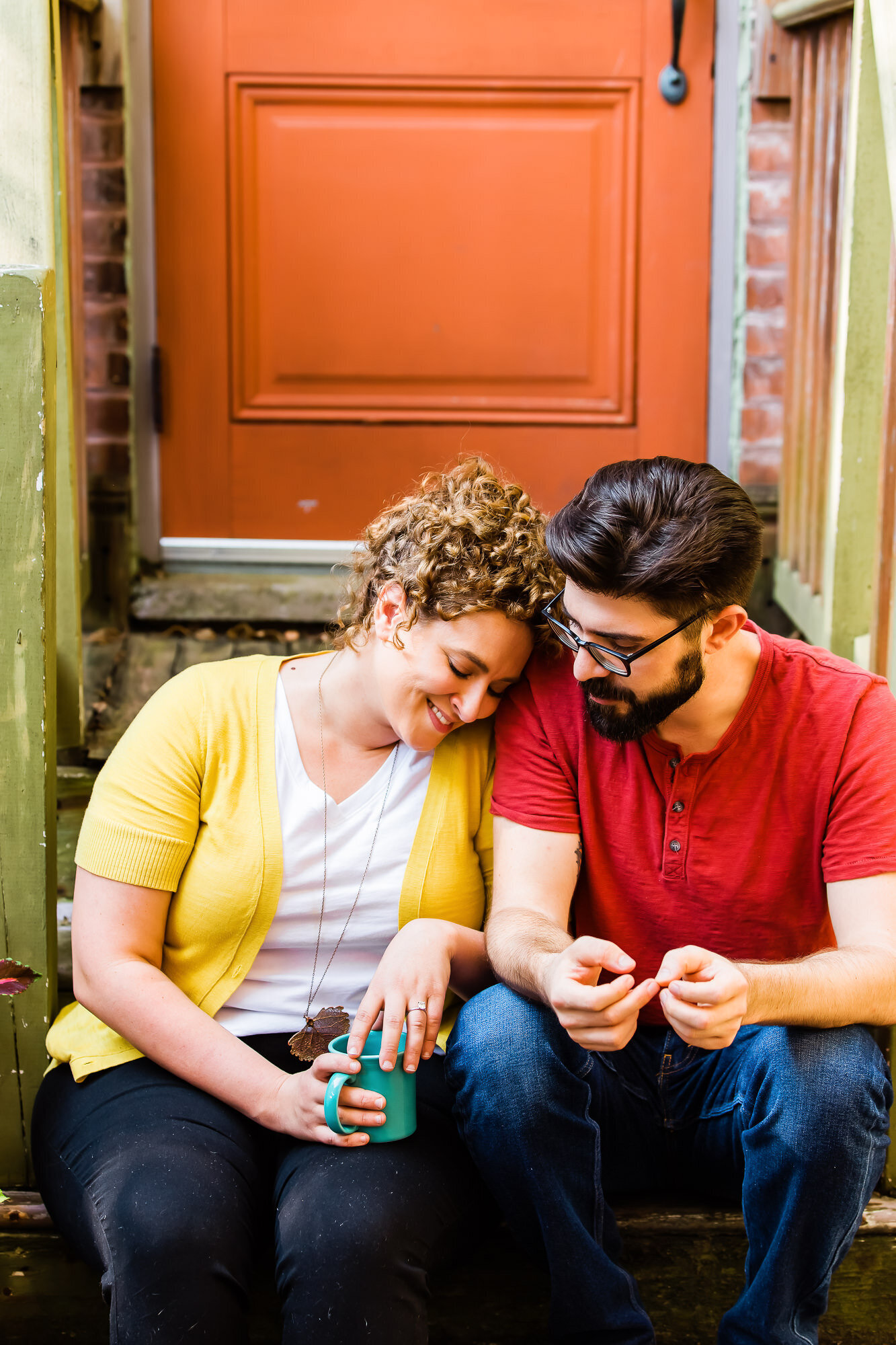 Candid engagement photo of a couple sitting on steps drinking coffee at The Mudhouse in Saint Louis
