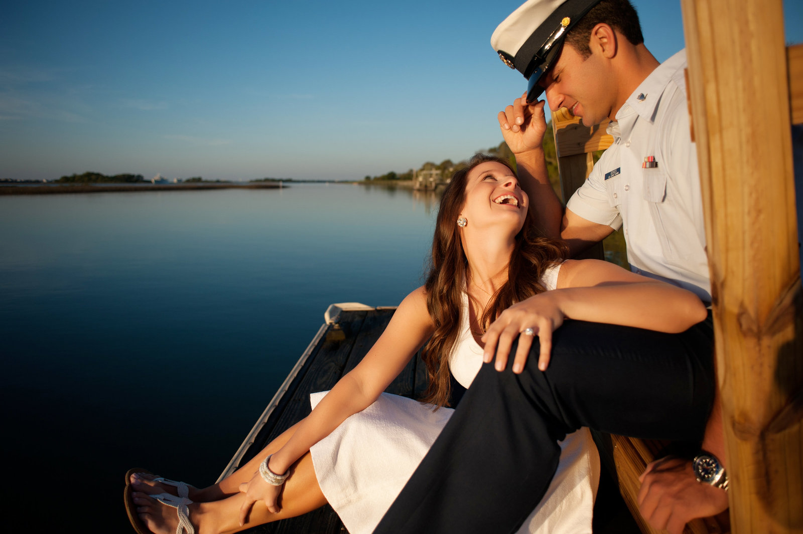a girl smiles at her fiance wearing his coast guard uniform as they sit on a dock on the intracoastal waterway