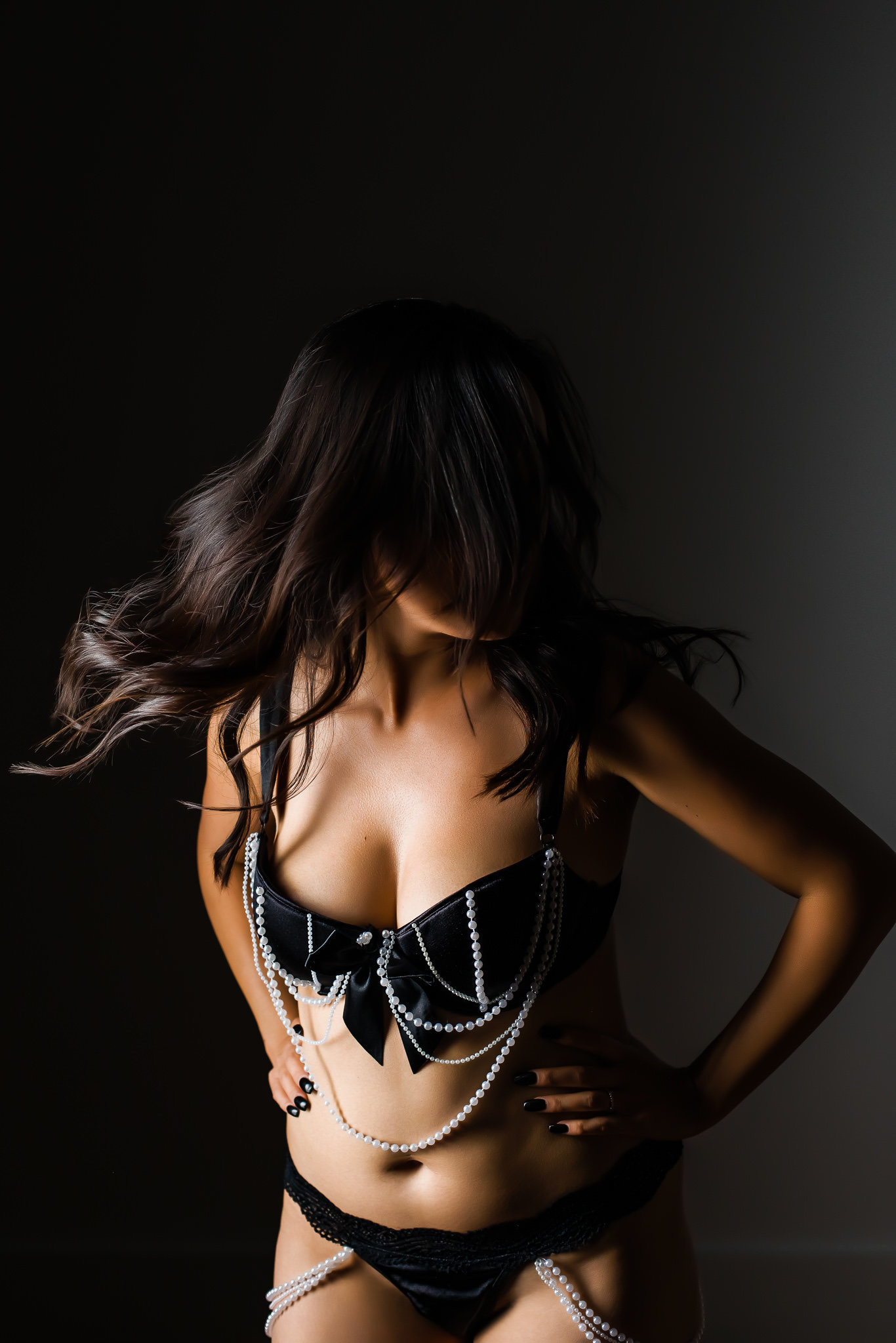 Boudoir photo in studio of a woman in lingerie flipping her hair