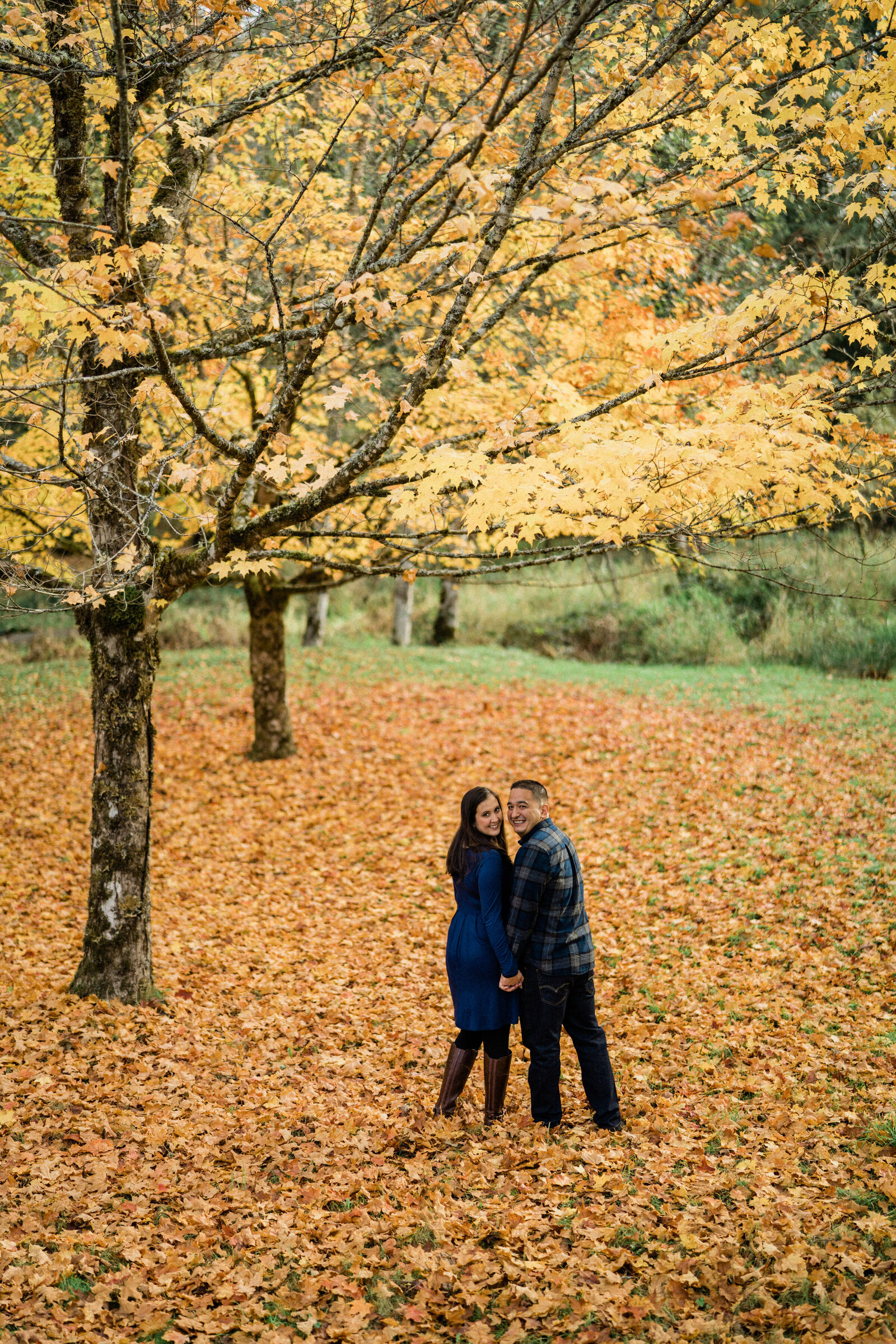 Fall leaves surround the couple at Rockwood Farm, best places for engagement photos in Seattle