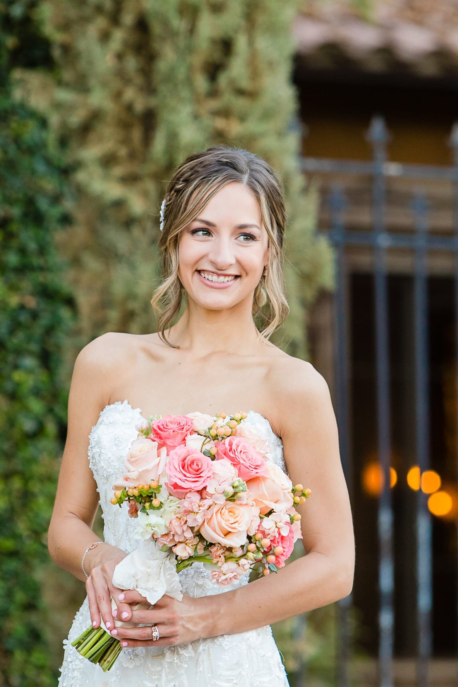 bride-smiling-holding-peach-and-pink-bouquet